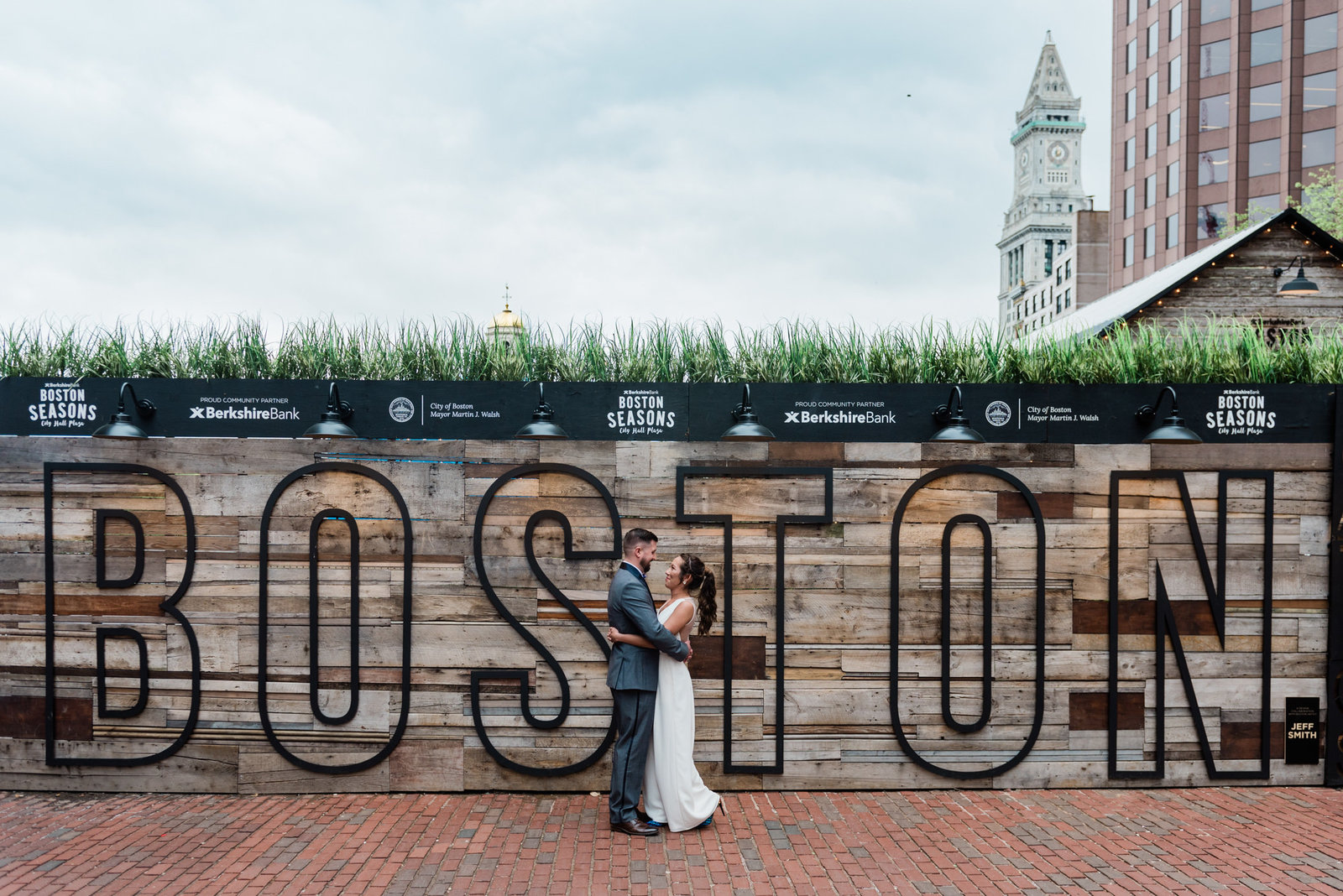 A photo in front of the Boston sign in downtown government center after a Boston city hall elopement