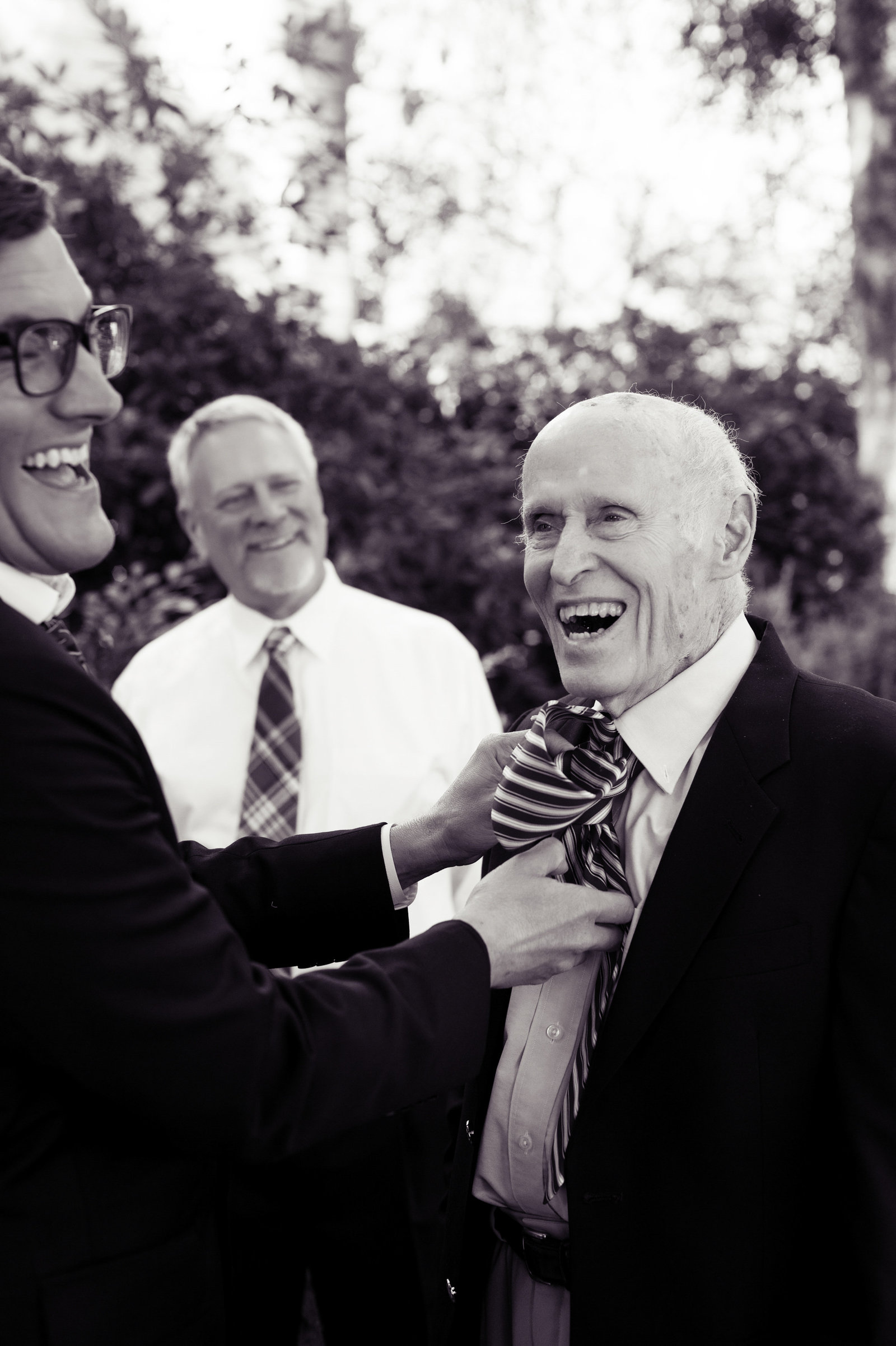 groom helps grandpa with tie
