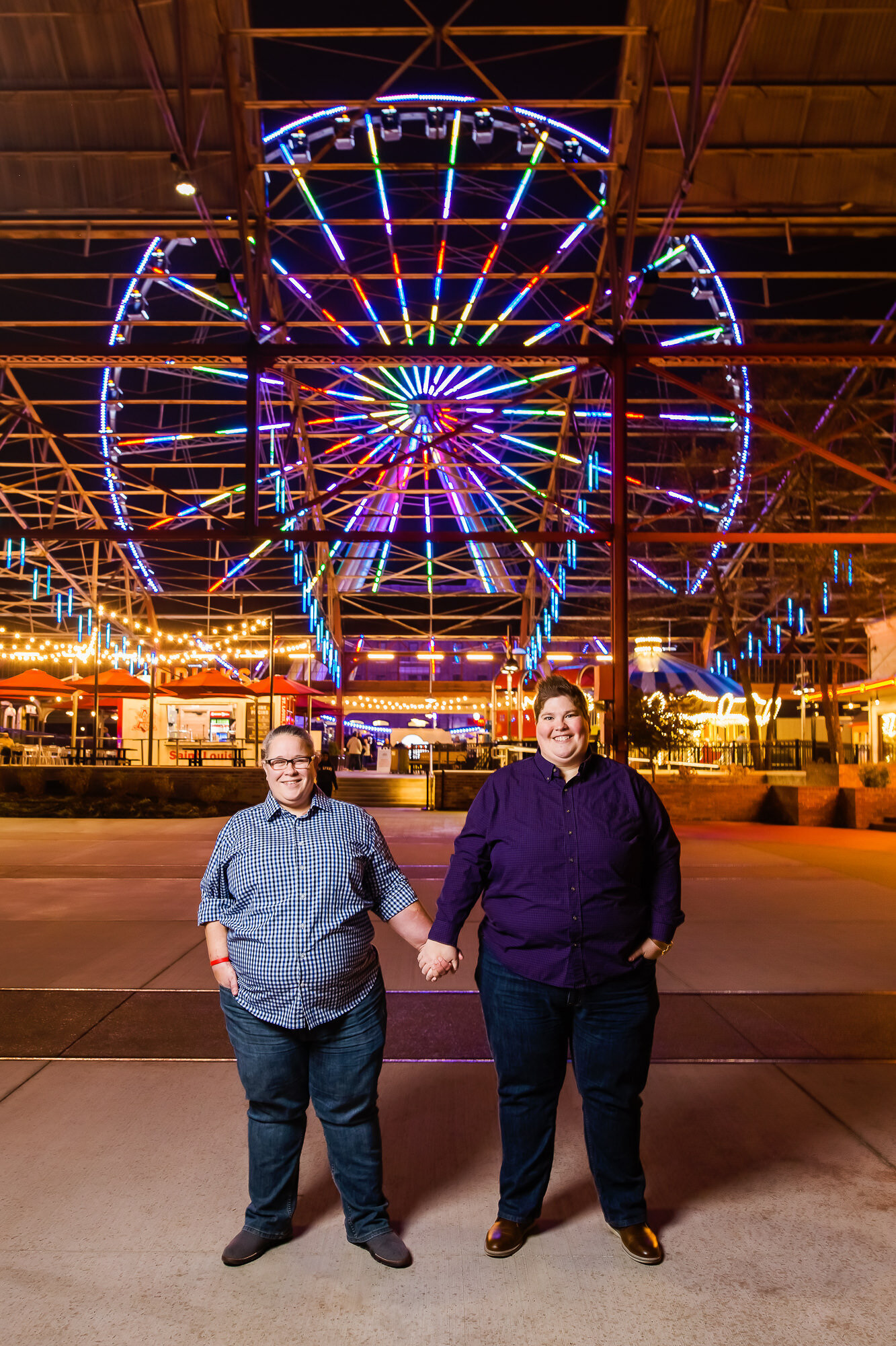 Same sex couple poses for an engagement photo in front of The St. Louis Wheel in downtown Saint Louis