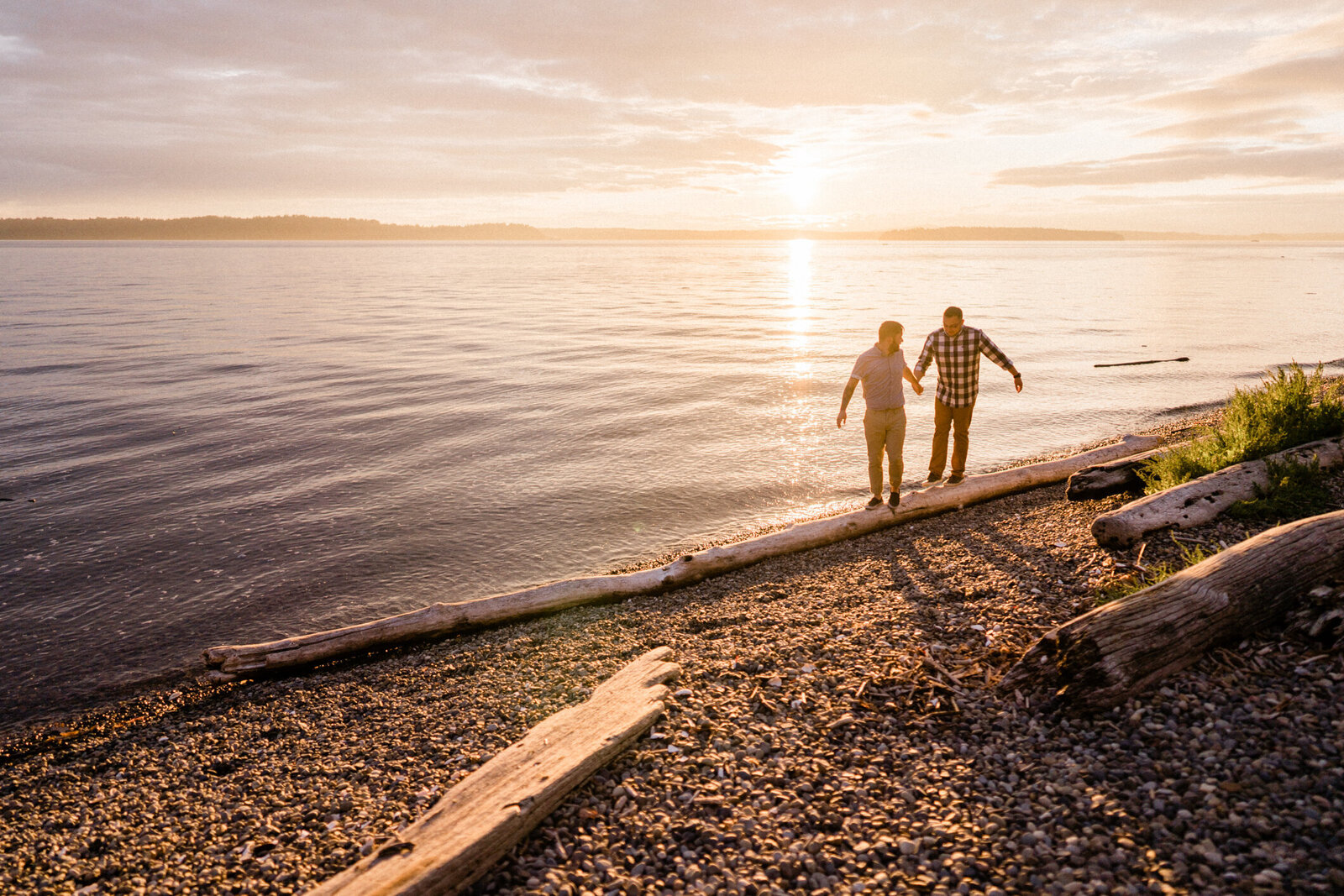 Couple balancing on a log along Puget Sound, one of the top places for engagement and wedding pictures in Seattle