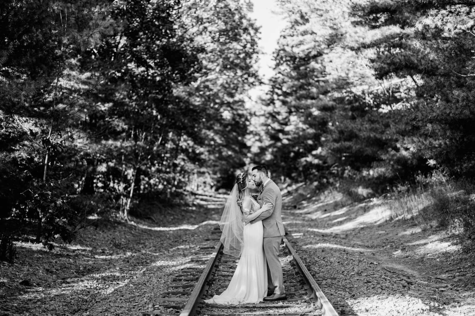 couple kissing on railroad
