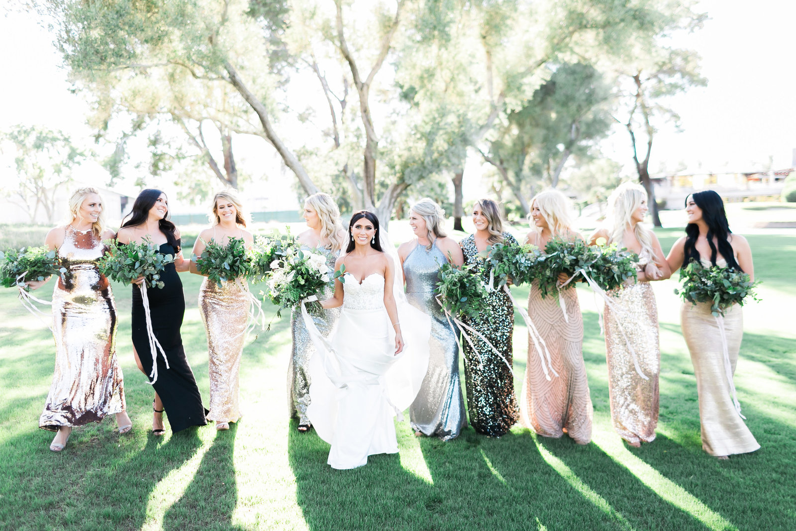 a photo of a bride and her bridal party dressed in mixed metallic dresses  on a grass lawn at the Las Vegas Country Club