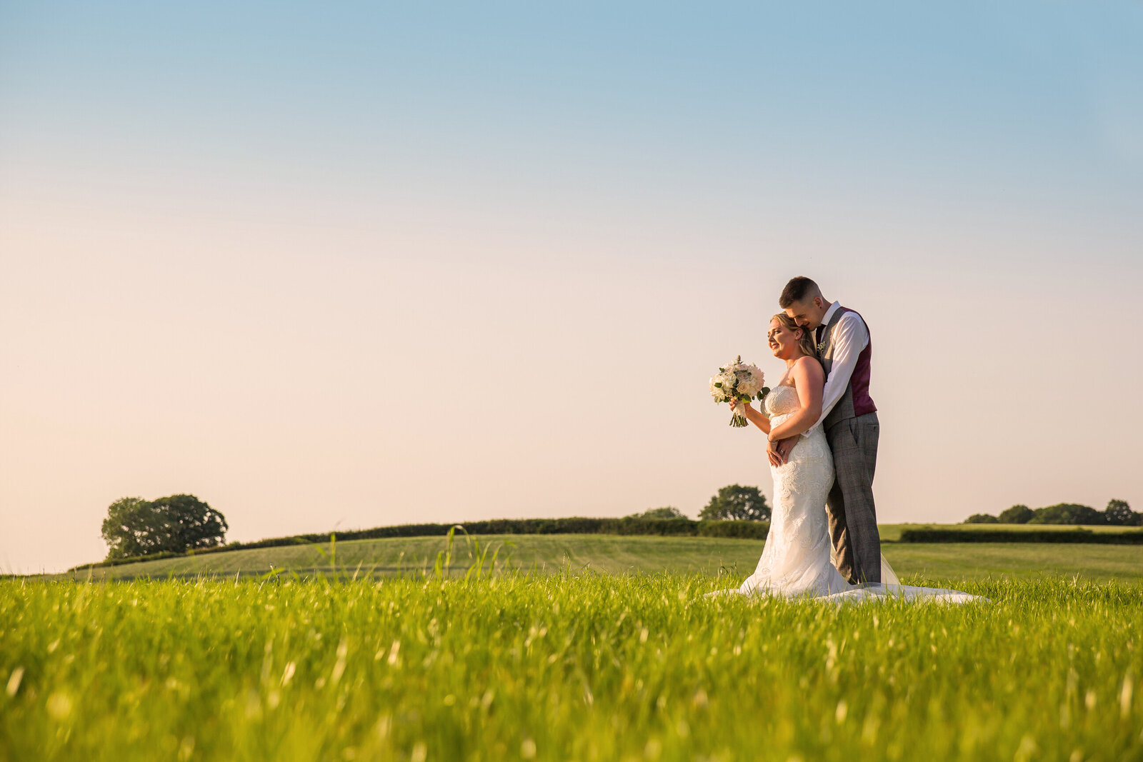 Wedding photography of bride and groom hugging in a field in the summer. Photography by Lynsey Grace Photography