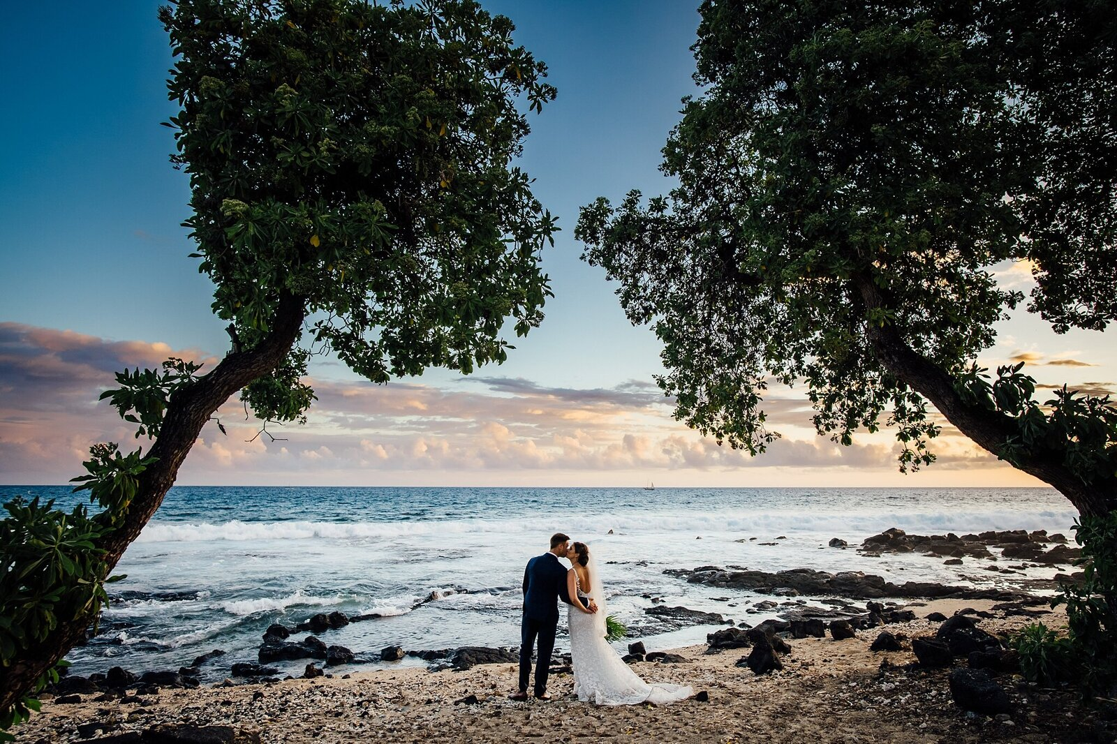 couple kissing under trees on beach