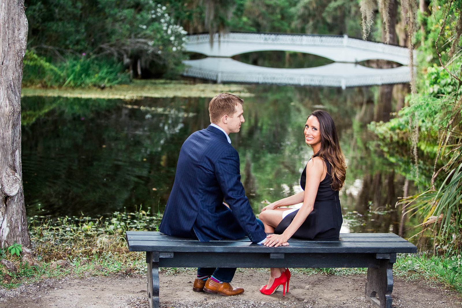 Engaged couple sit on a bench by the white bridge, Magnolia Plantation, Charleston Engagement Photographer.