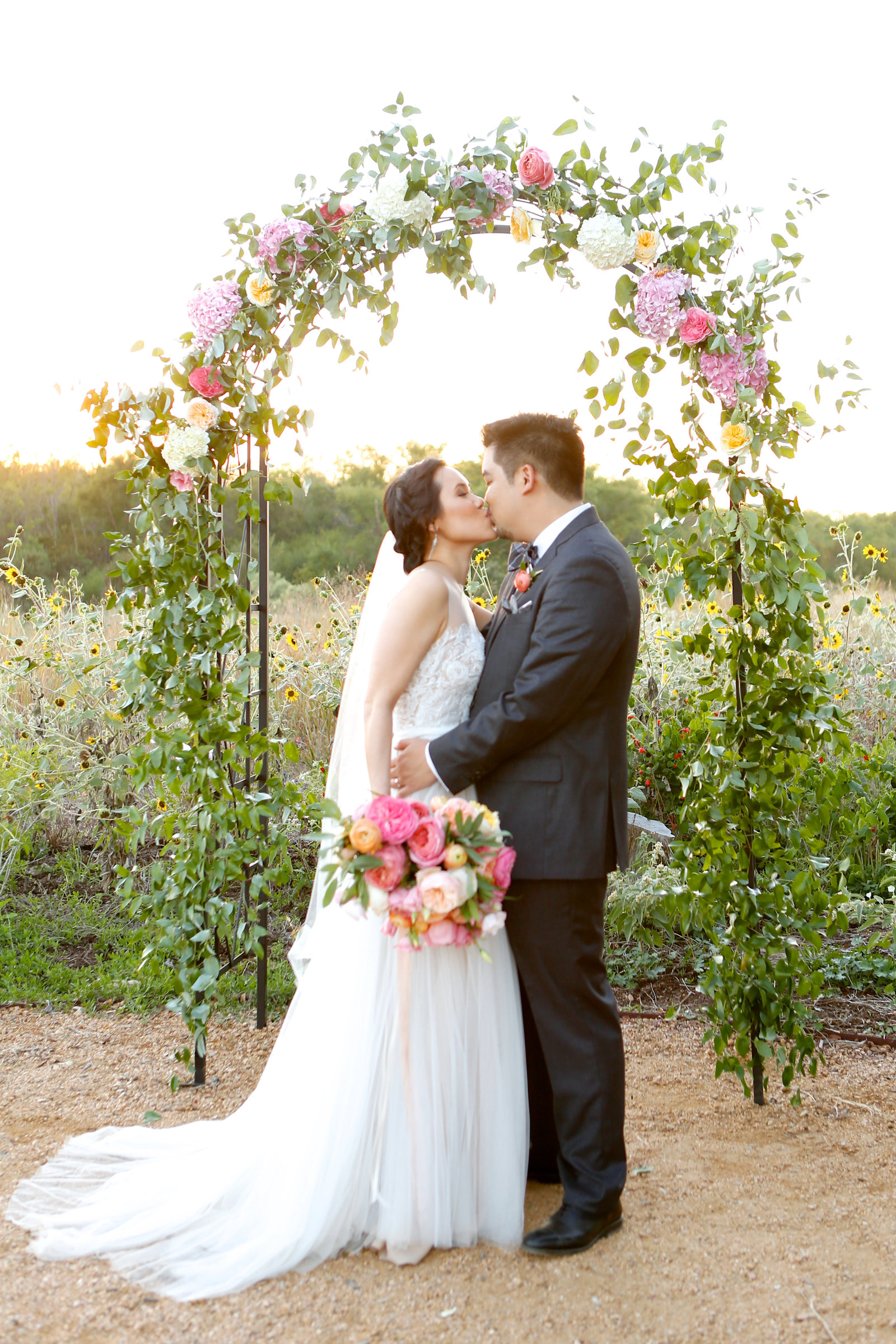 bride and groom in front of colorful floral arch