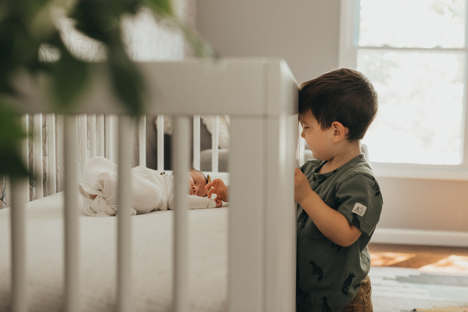 brother reaching through crib to baby