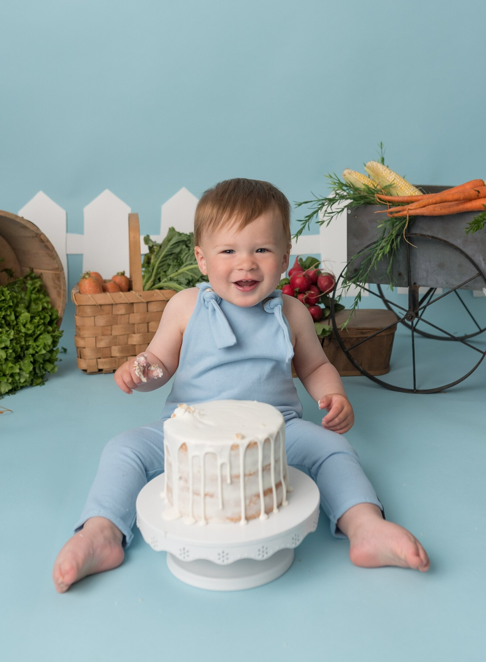Little boy having his pictures taken for a Peter Rabbit themed cake smash