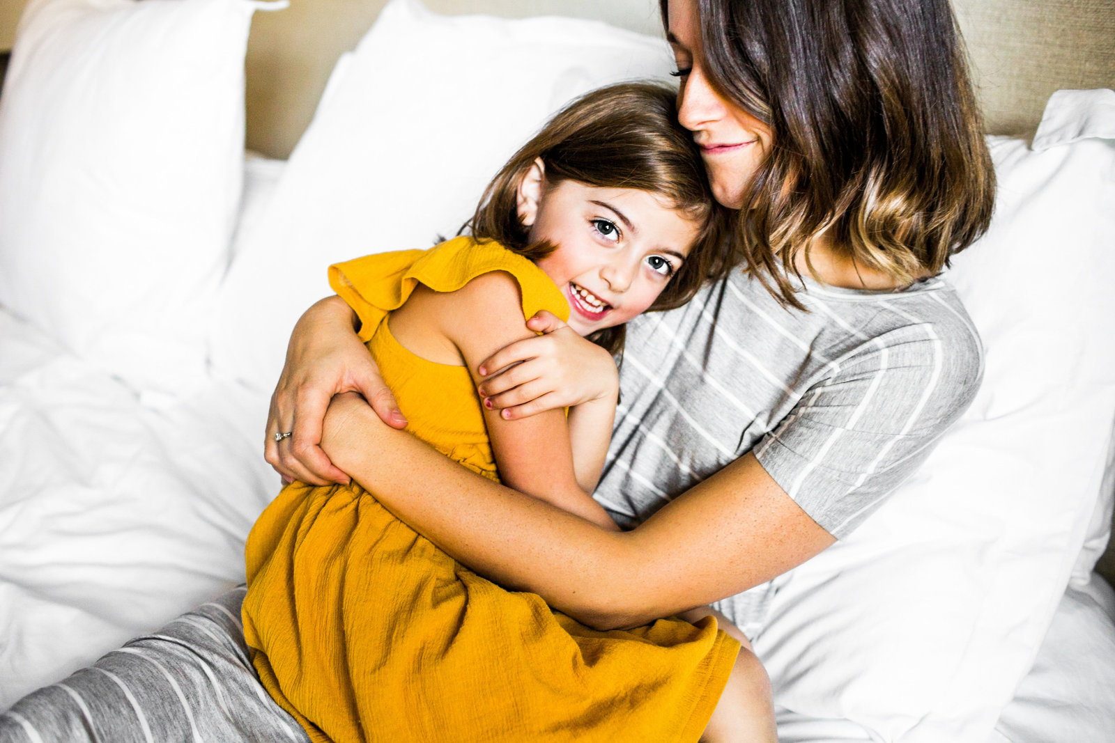 Mom snuggling with her daughter at home in bed