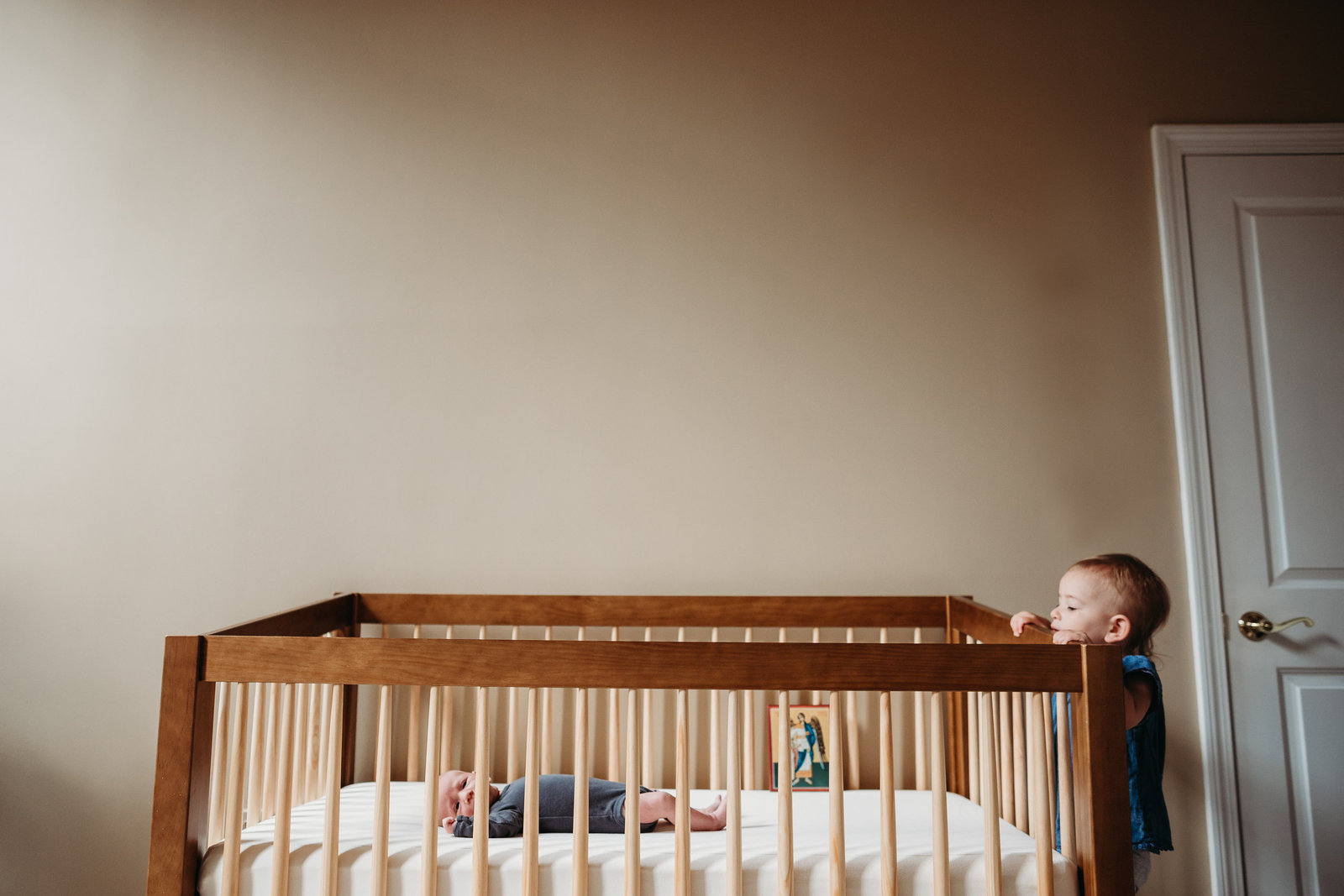 toddler peeks over top of crib to look at baby brother