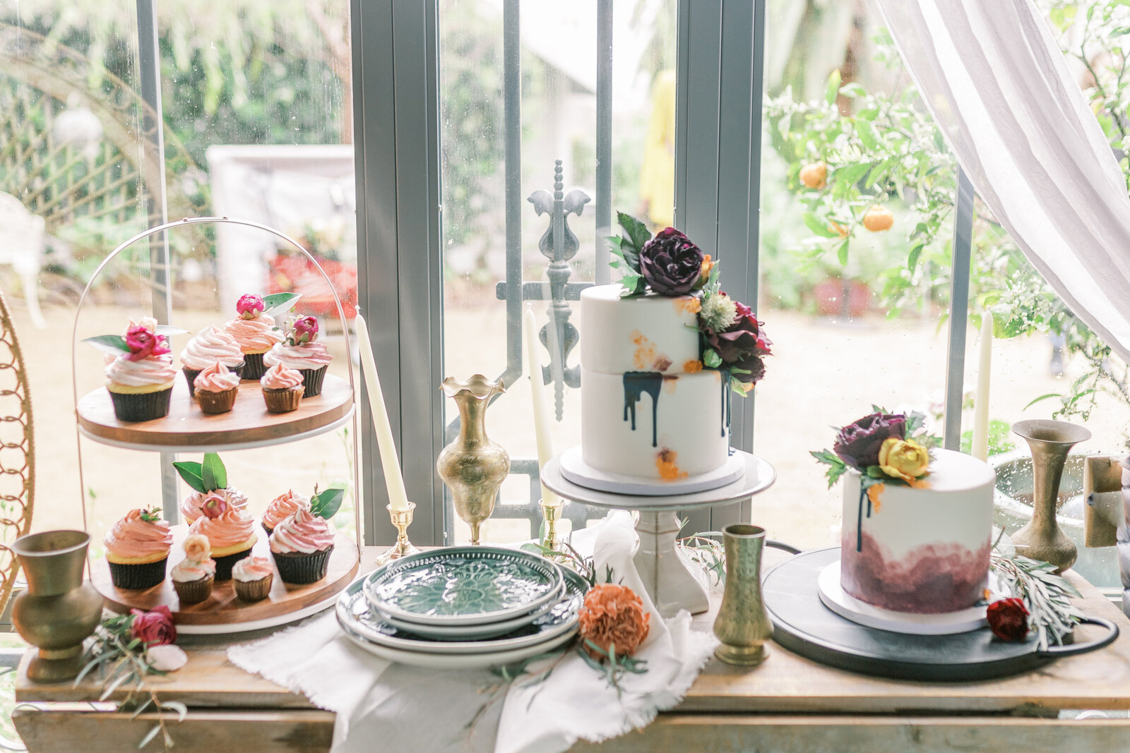 Dessert table with cakes, cupcakes, and florals