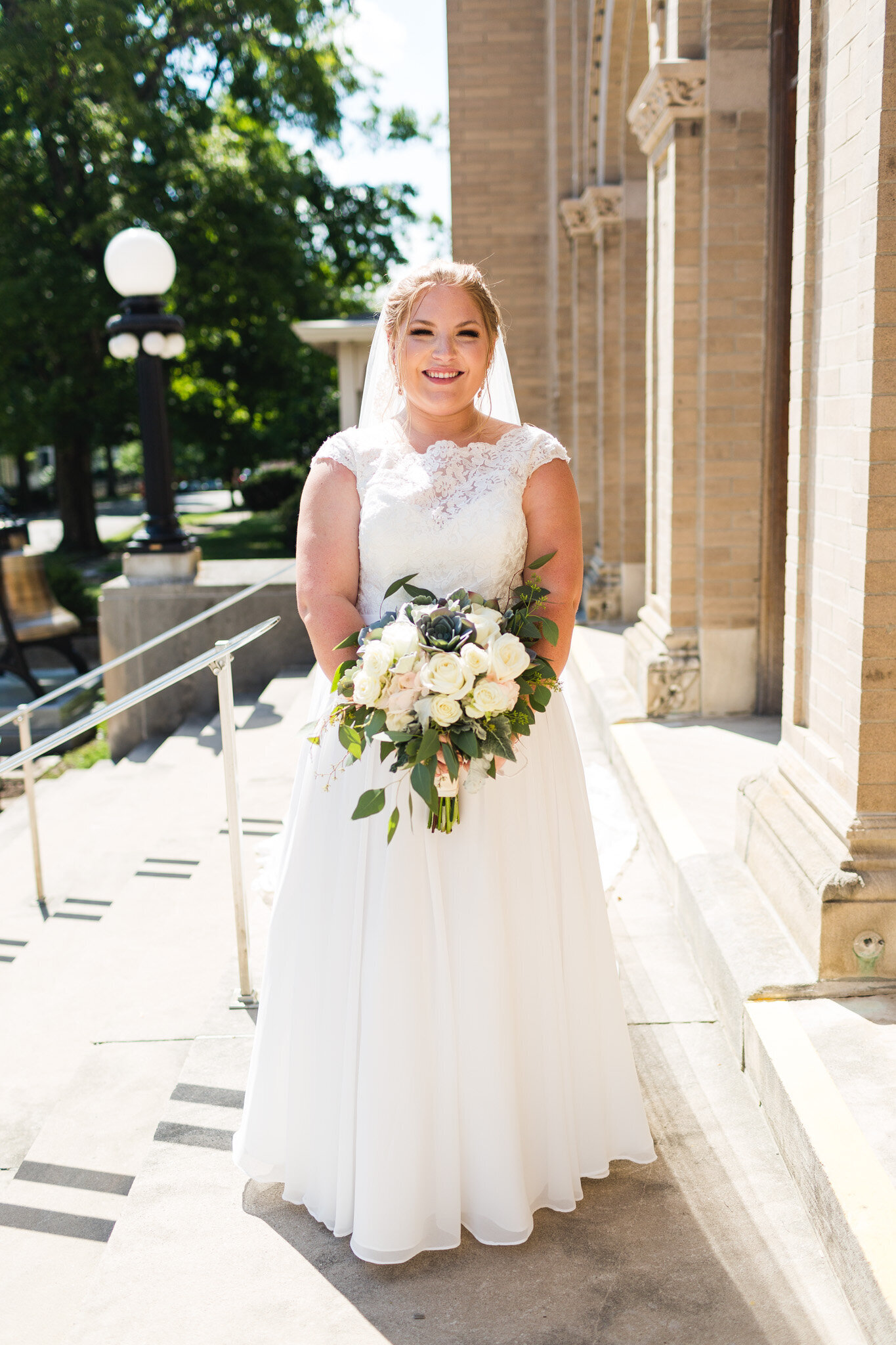 bride smiling outside of church for portrait with veil and flowers ohio