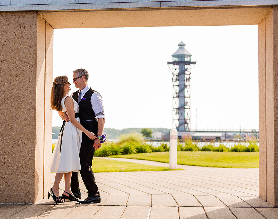Bride and groom embrace in alcove with Bicentennial Tower in the background