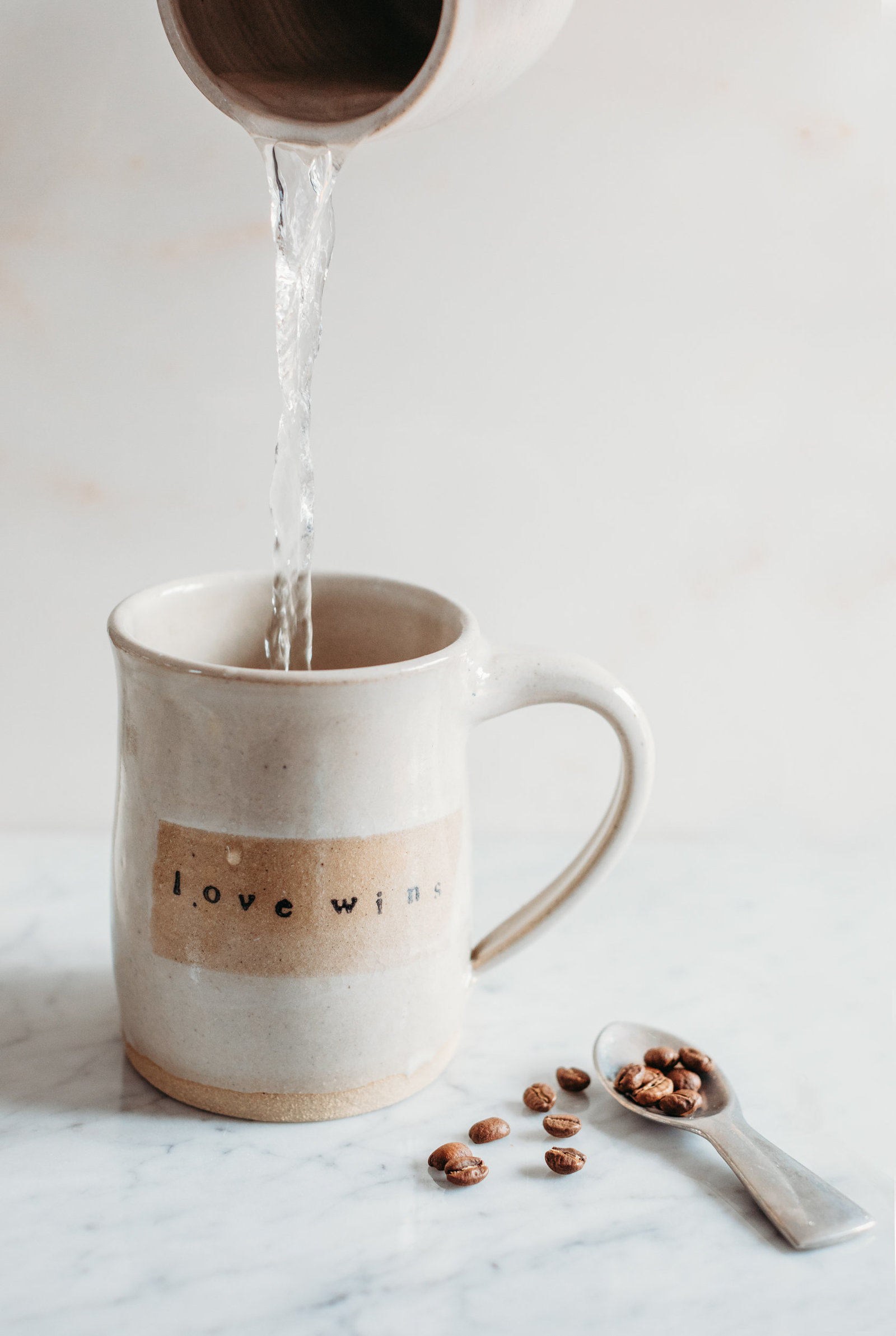 product shot of a tan coffee mug and coffee beans
