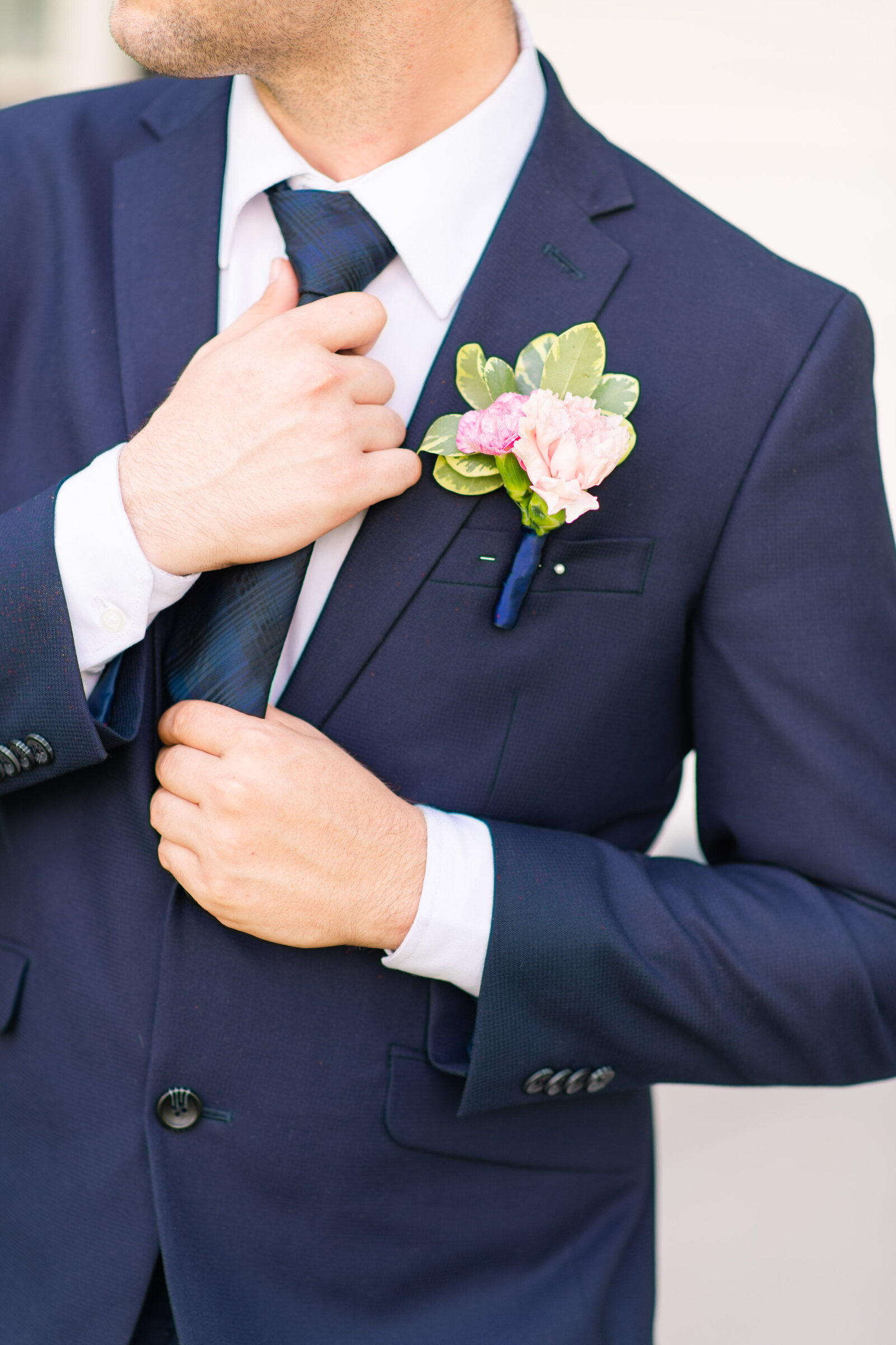 groom in dark blue suit adjusting his tie