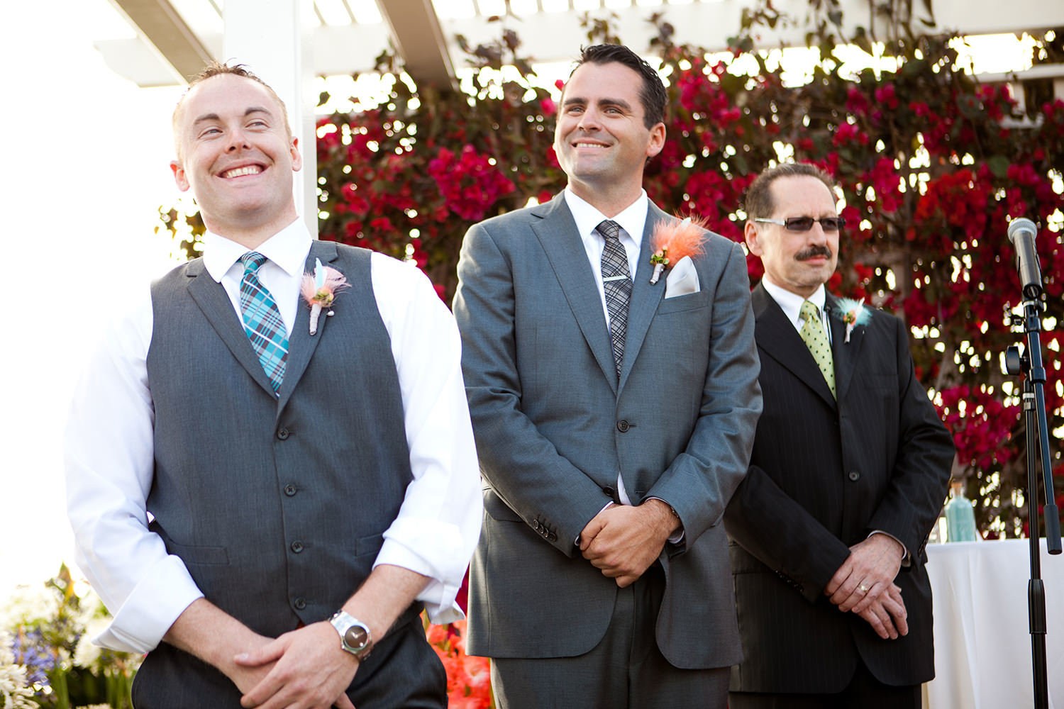 groom smiling while bride walks down the aisle