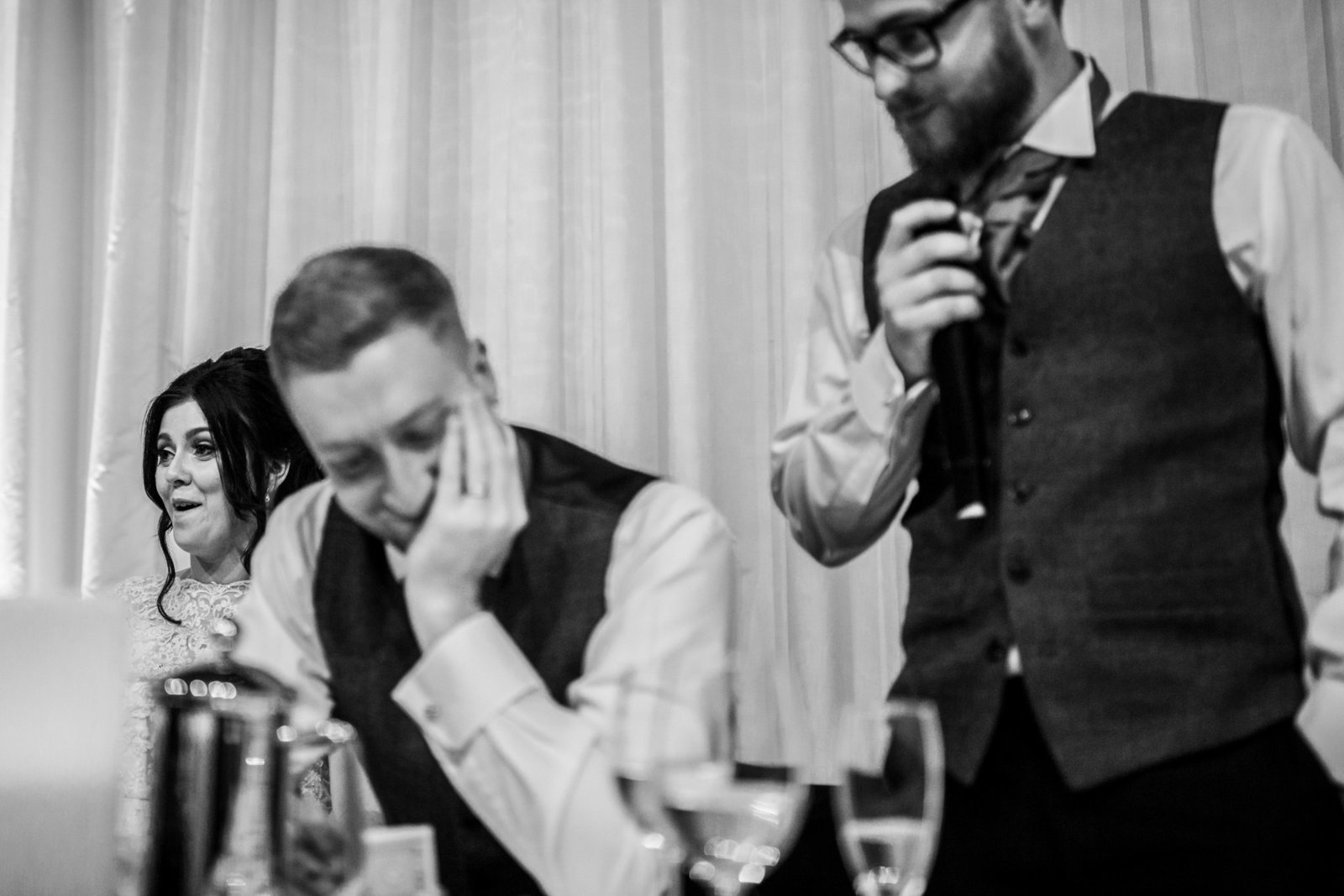 The Bestman is giving his speech at a wedding venue in Norfolk. The Grooms looks embarrassed and the Bride looks shocked.