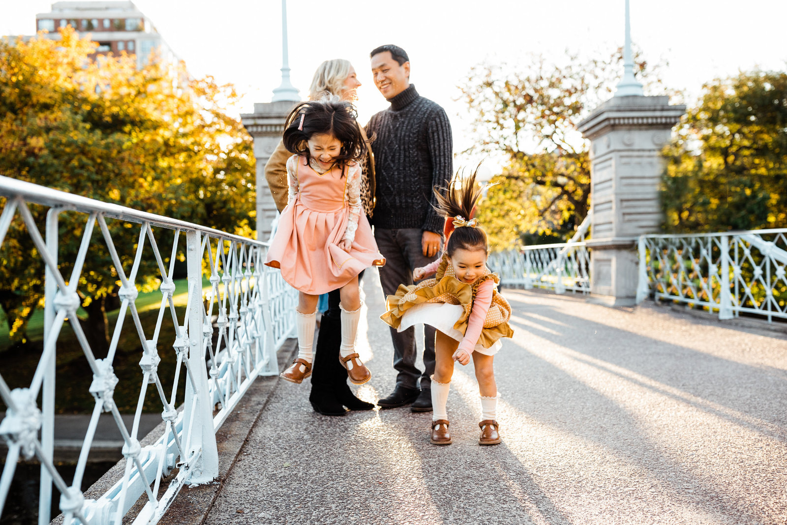 two sisters jump on a bridge in boston public garden family session