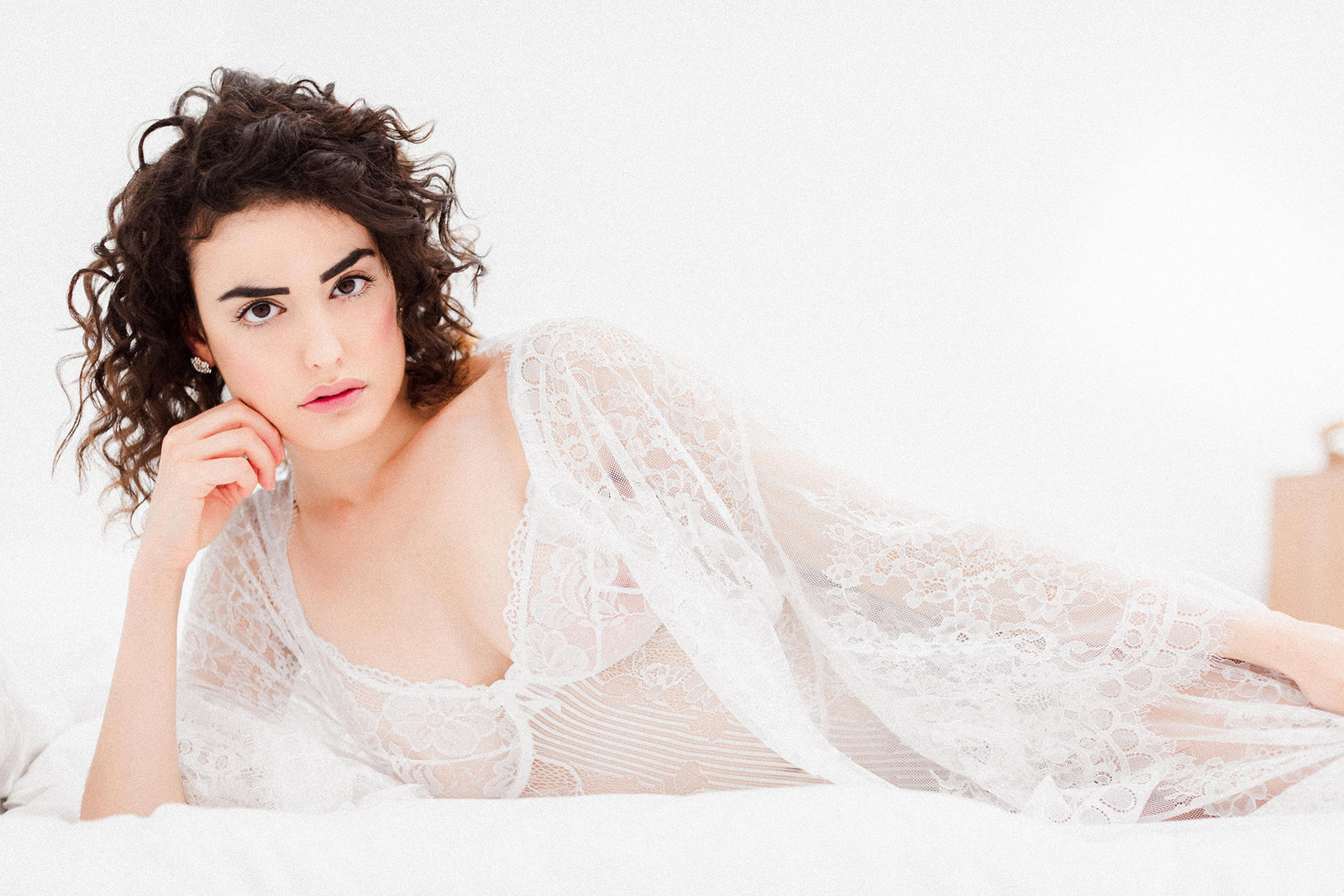 bride in lace white lingerie laying on bed