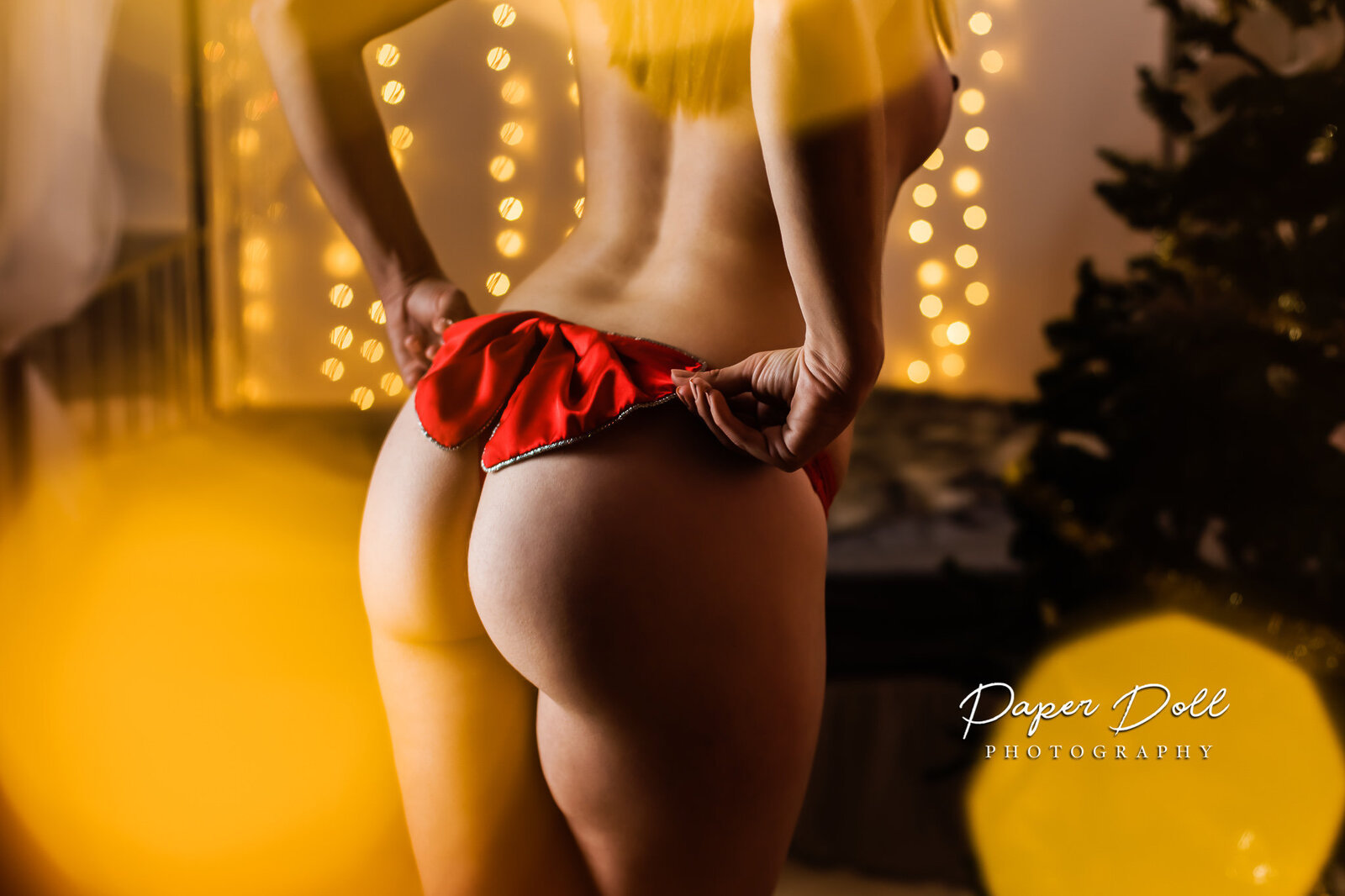 Christmas boudoir photo with a bow on a woman's butt