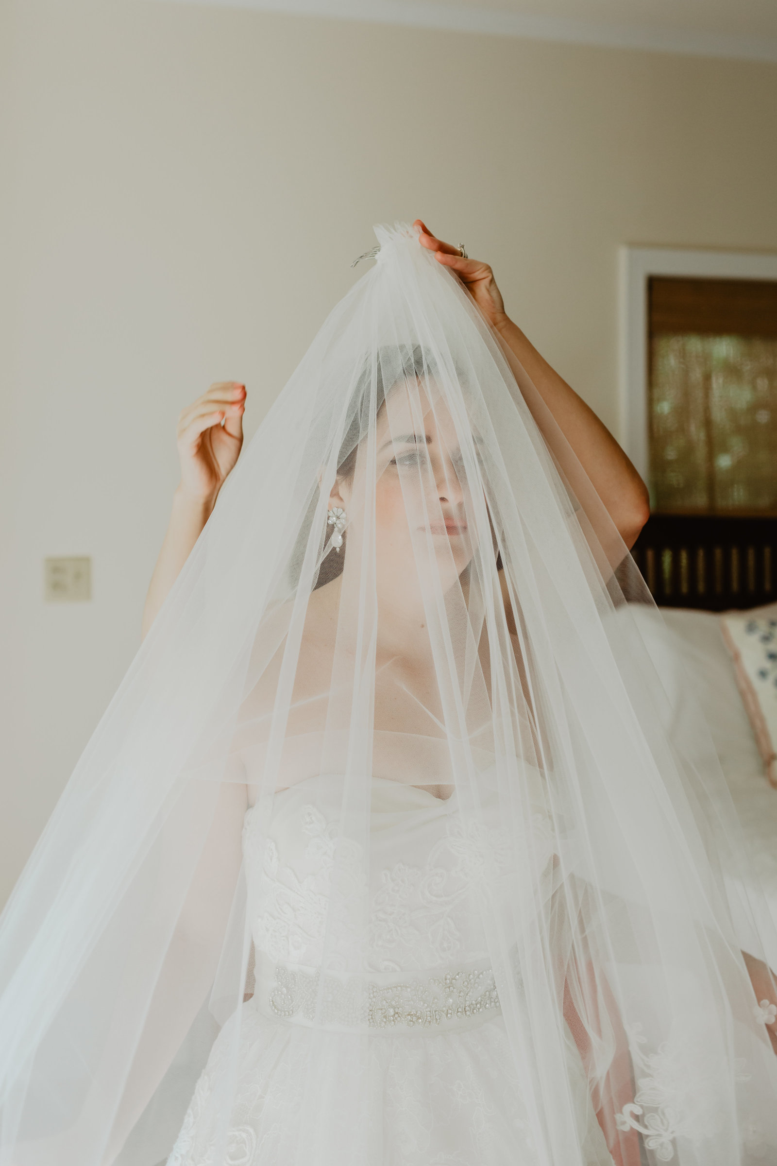Bride have her veil put on by maid of honor in Magnolia Springs