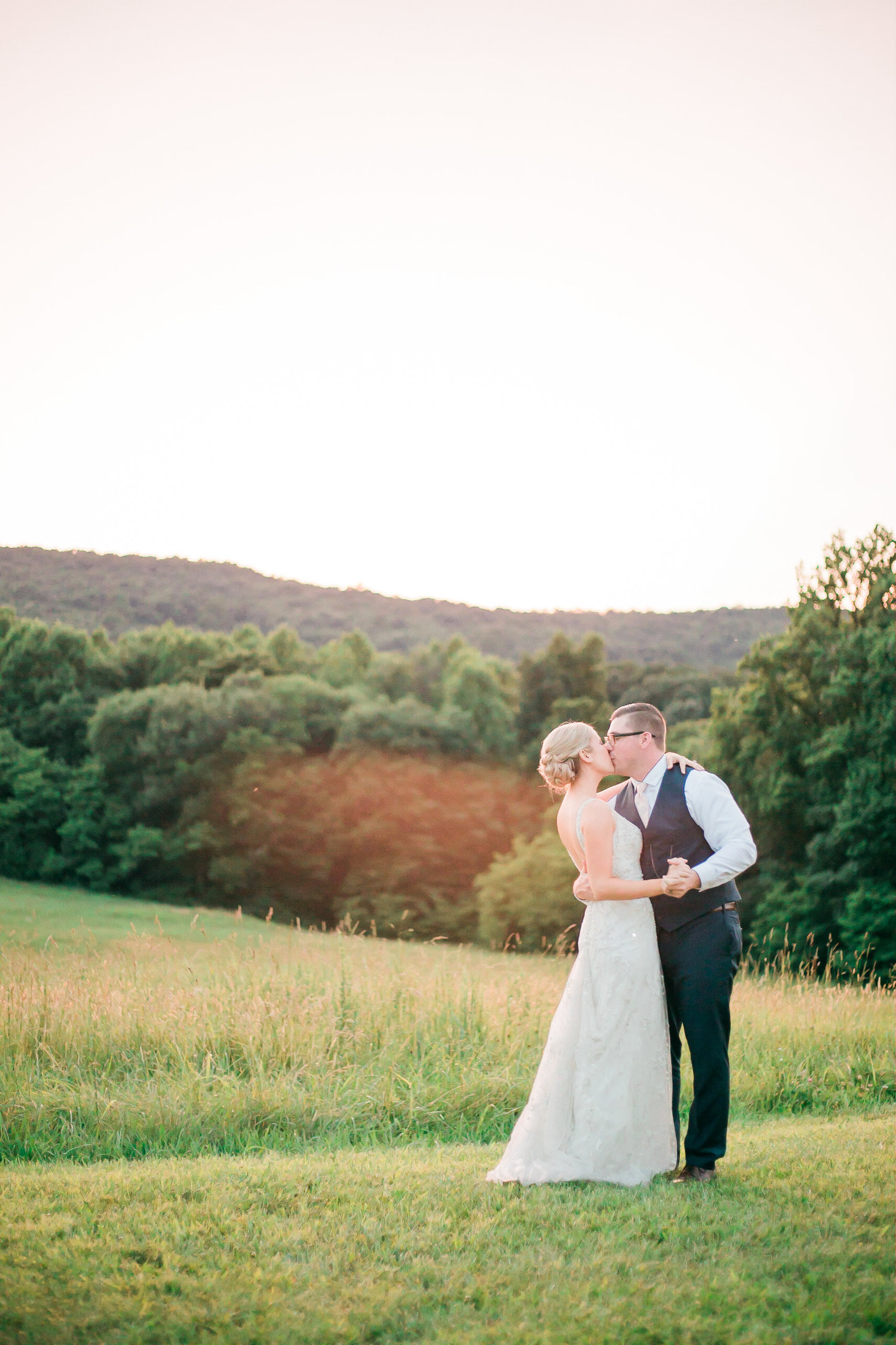 Bride and groom embrace in a golden field at Springfield Manor Maryland