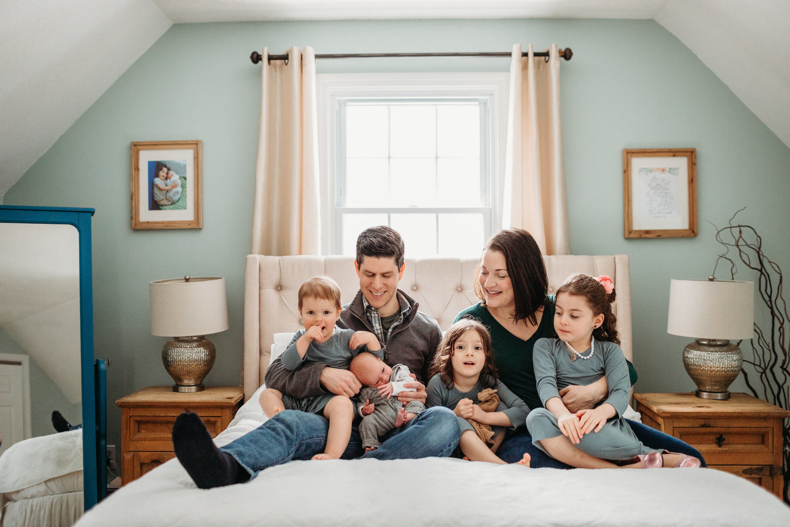 family of six sit on bed for newborn pictures in bolton ma