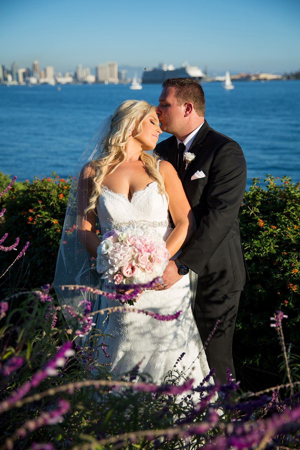 bride and groom with san diego skyline in background