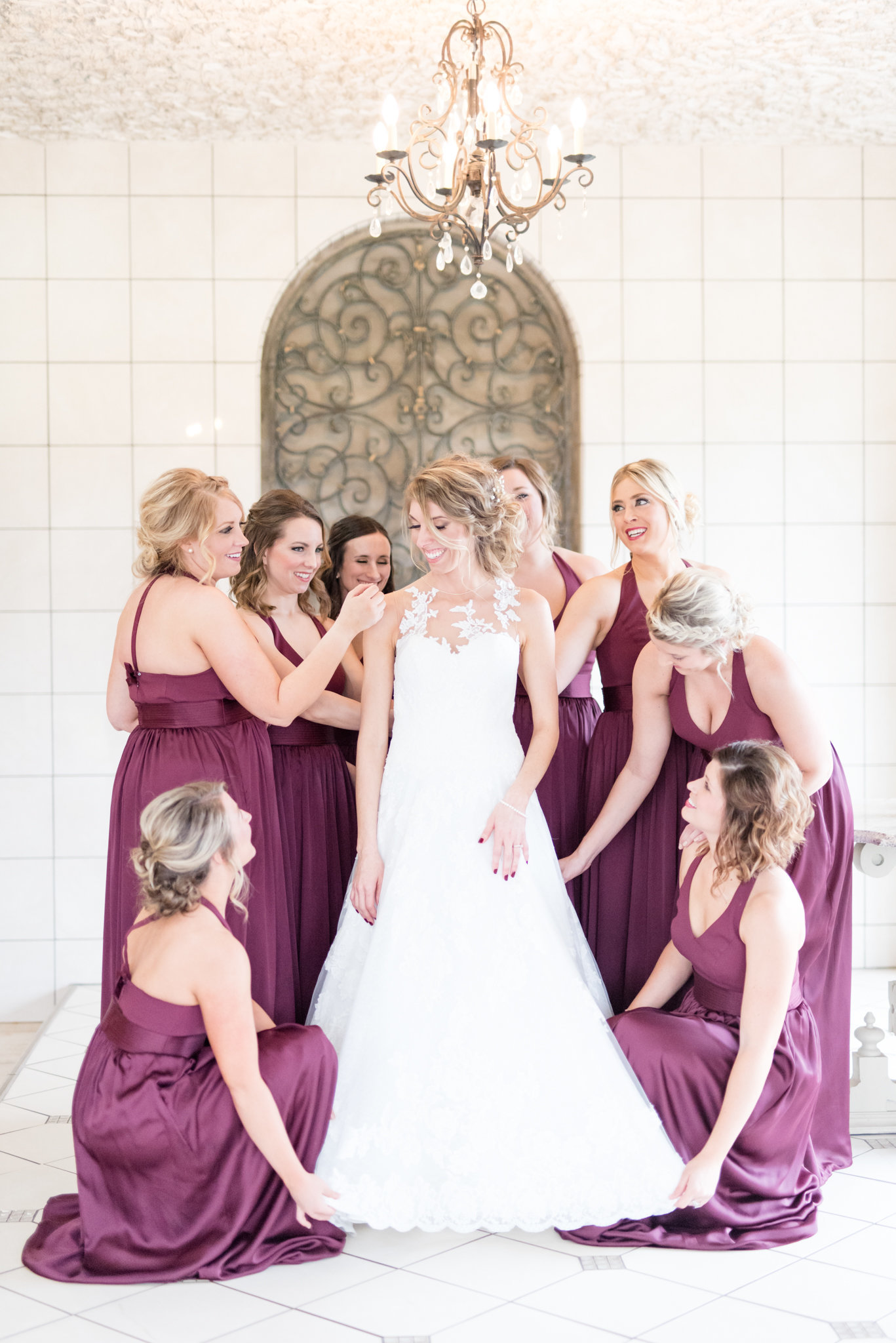 Bridesmaids stand around bride and help her get ready.