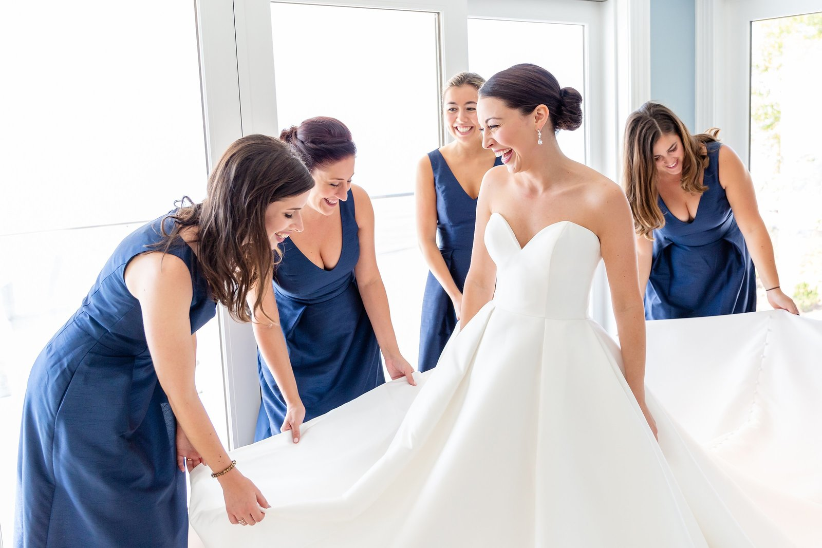 Bride-surrounded-by-her-bridesmaids-fixing-her-dress-and-making-sure-she-looks-her-best