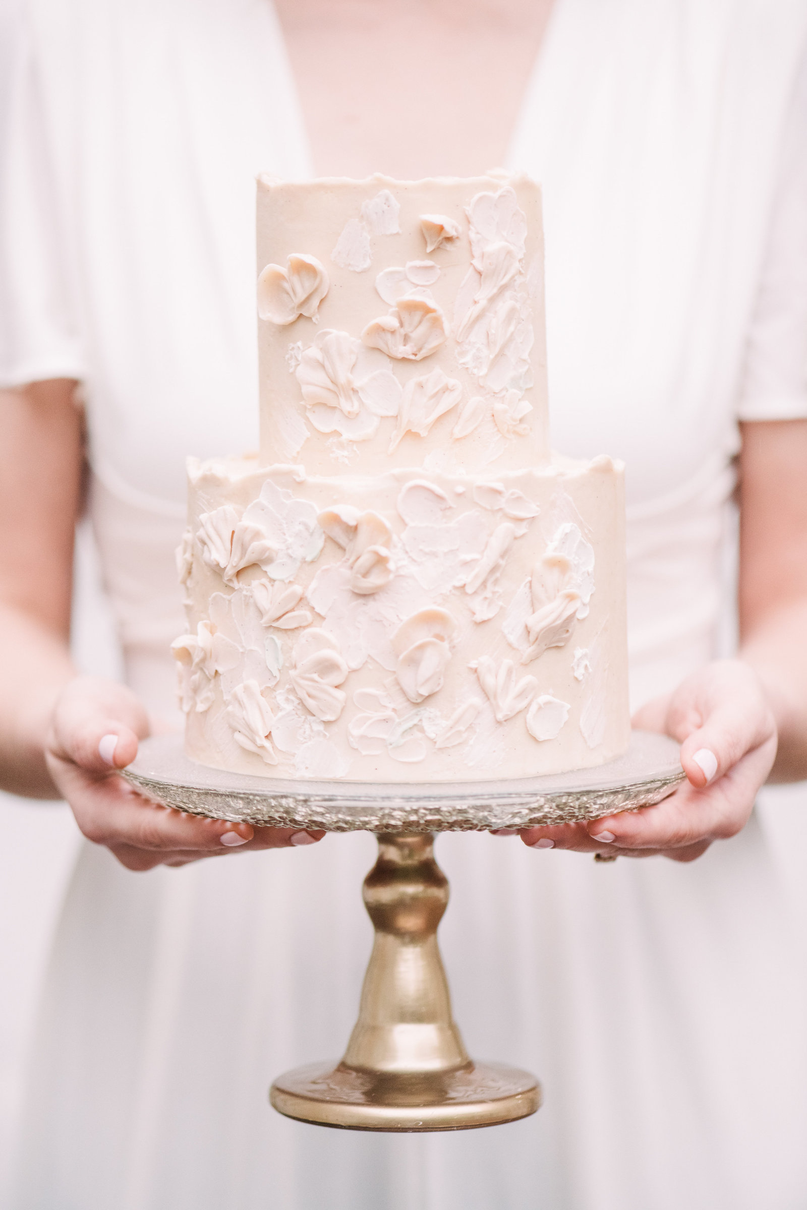 bride holding a soft pink wedding cake with organic painted flowers