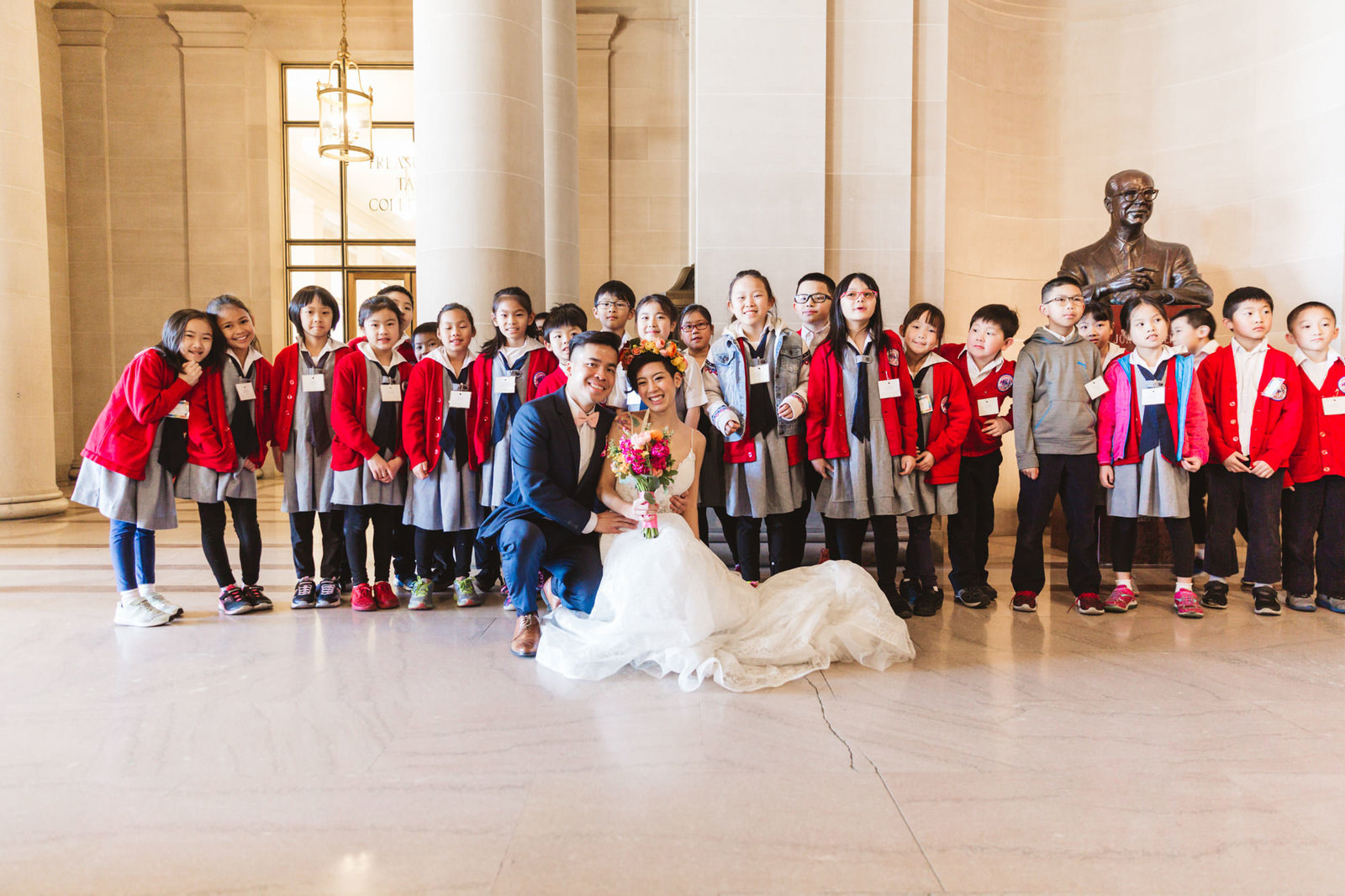 wedding photo at san francisco city hall with a huge group of schoolchildren on a school trip