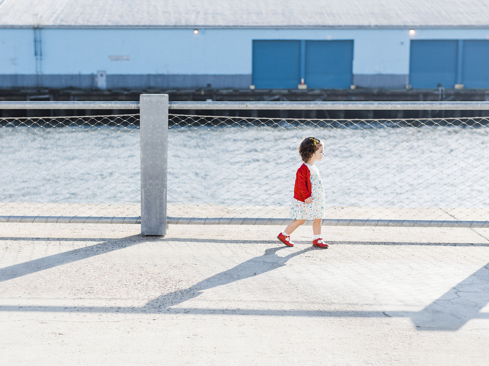 Little girl in red sweater walking by the water