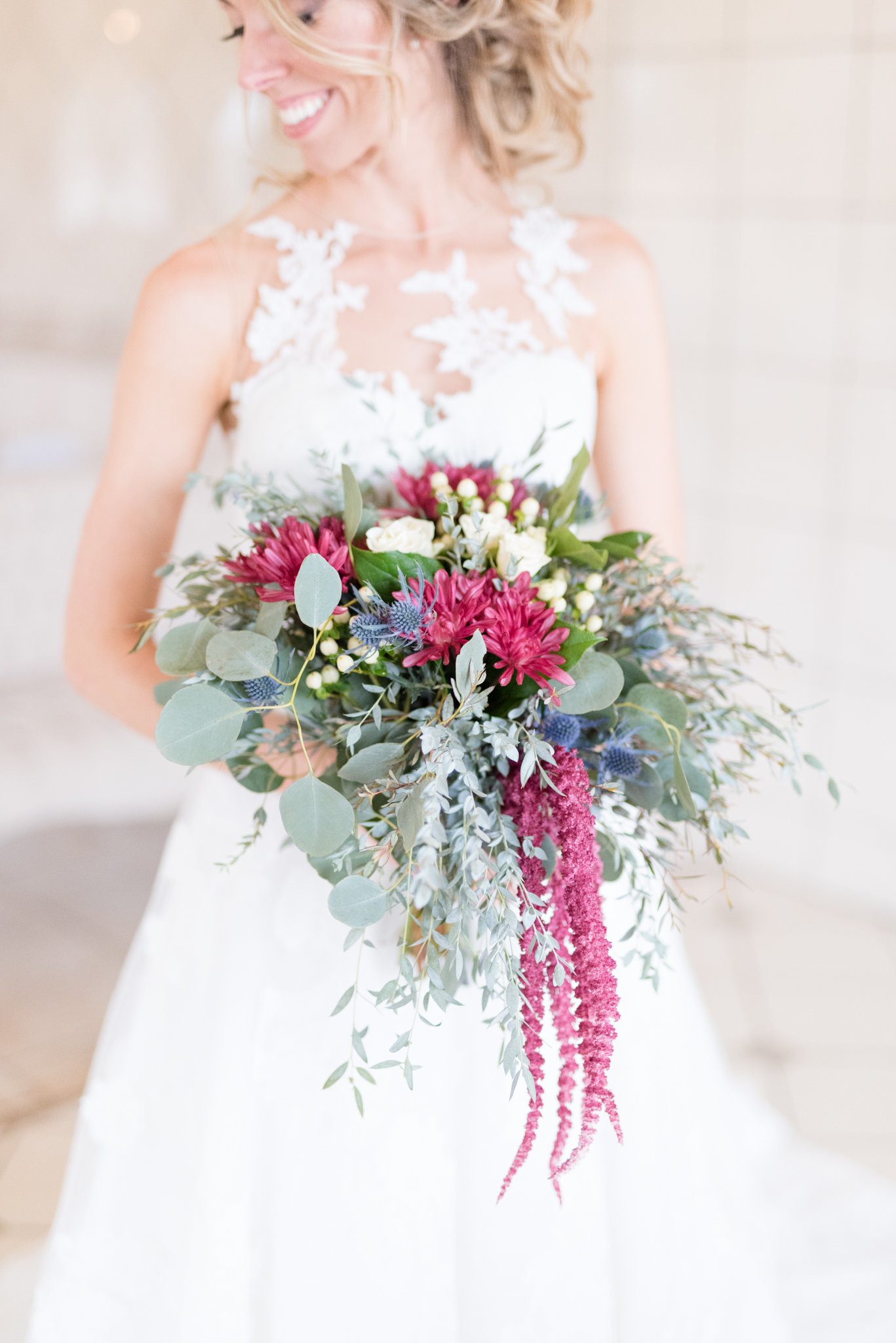 Bride holds Pink and cream wedding bouquet.