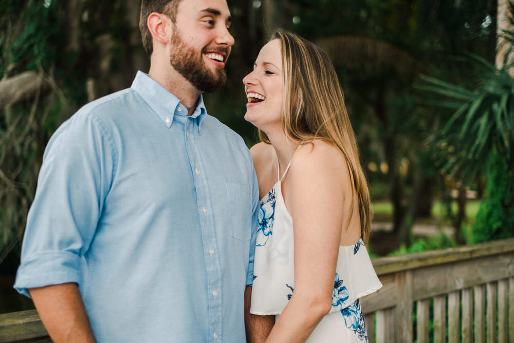 Couple laugh with each other at their engagement session at Kraft Azalea Gardens in Winter Park FL