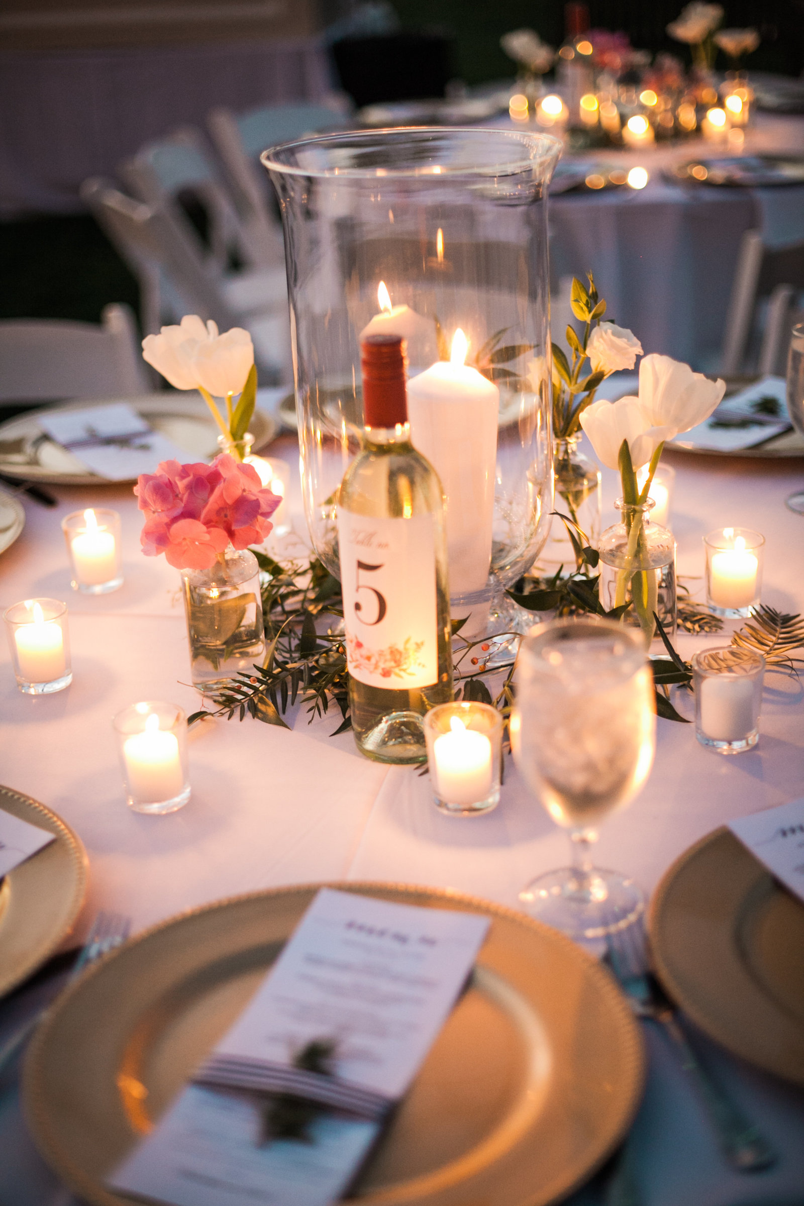wine bottles served as table numbers during the candlelit outdoor ceremony