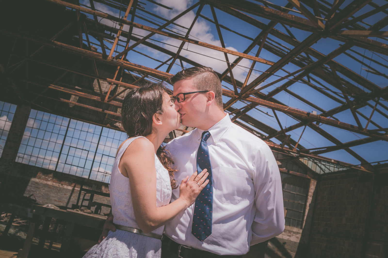 Couple kisses under airplane hanger in Connecticut.