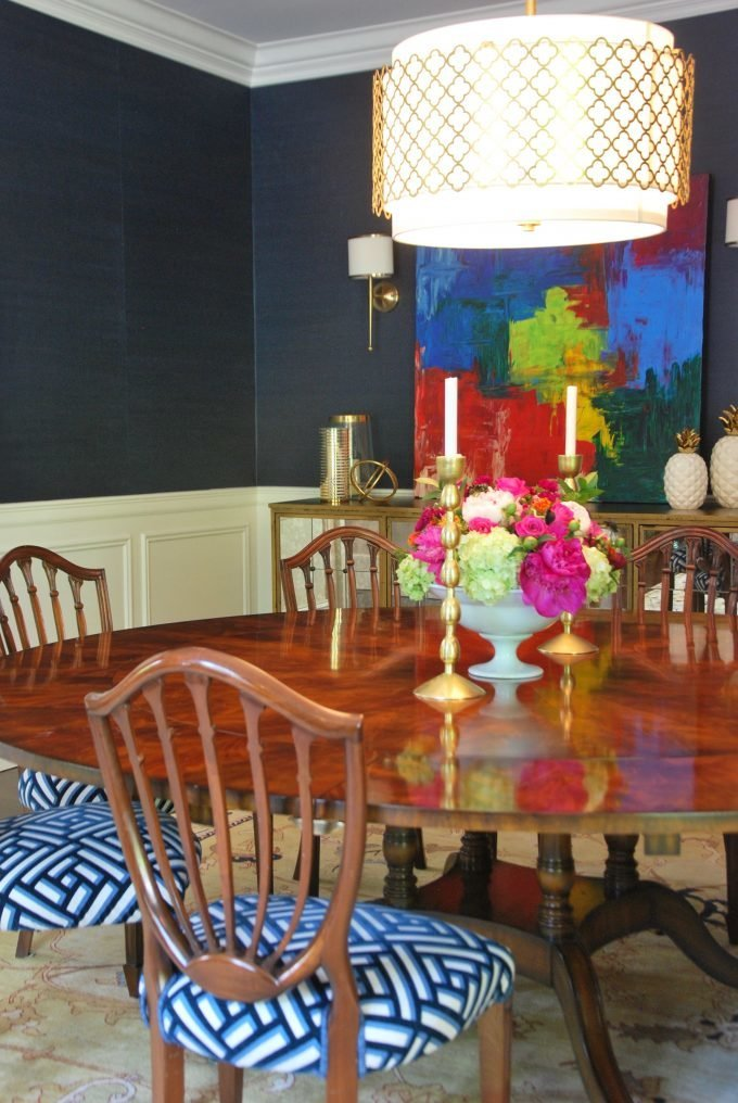 A navy formal dining room with a round wooden table and eight chairs.