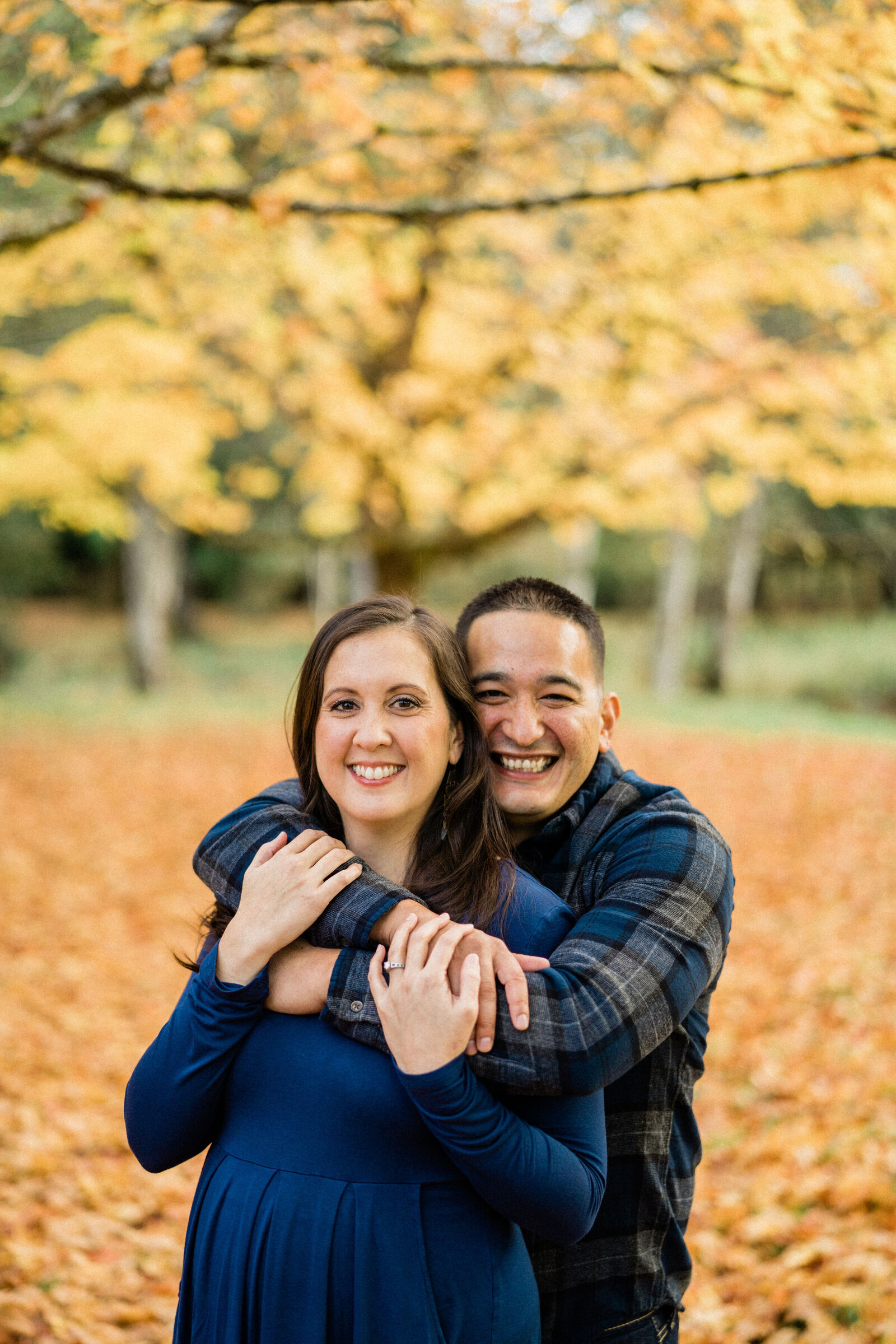 Couple hugging at Rockwood Farm, the best place for engagement photos in Seattle during fall color season