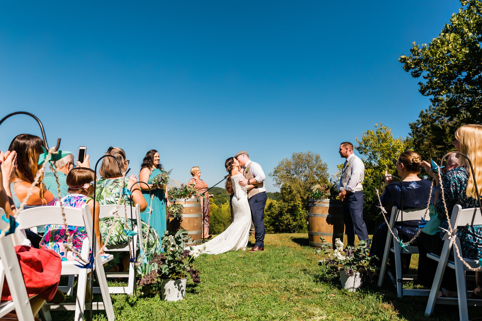 Bride and groom's first kiss at their wedding ceremony at Chaumette Winery neat St. Louis
