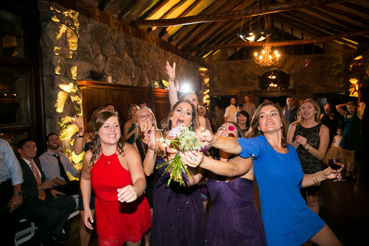 friends catching bouquet at reception