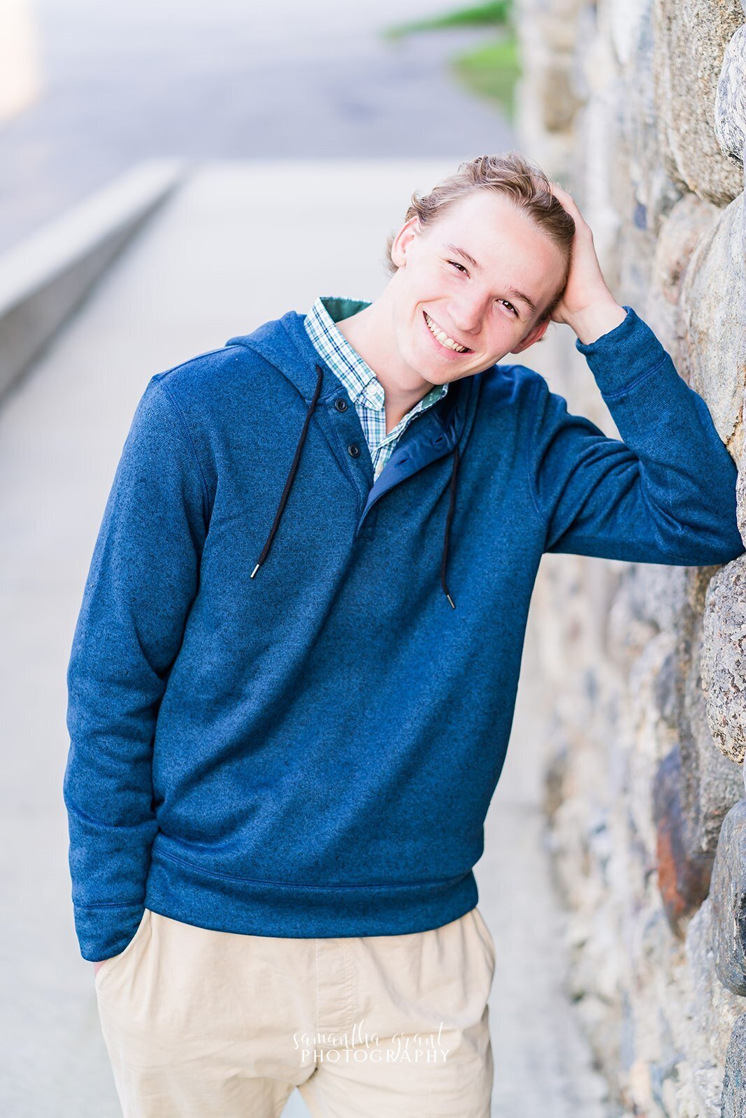 High school senior leaning against rock for senior photos