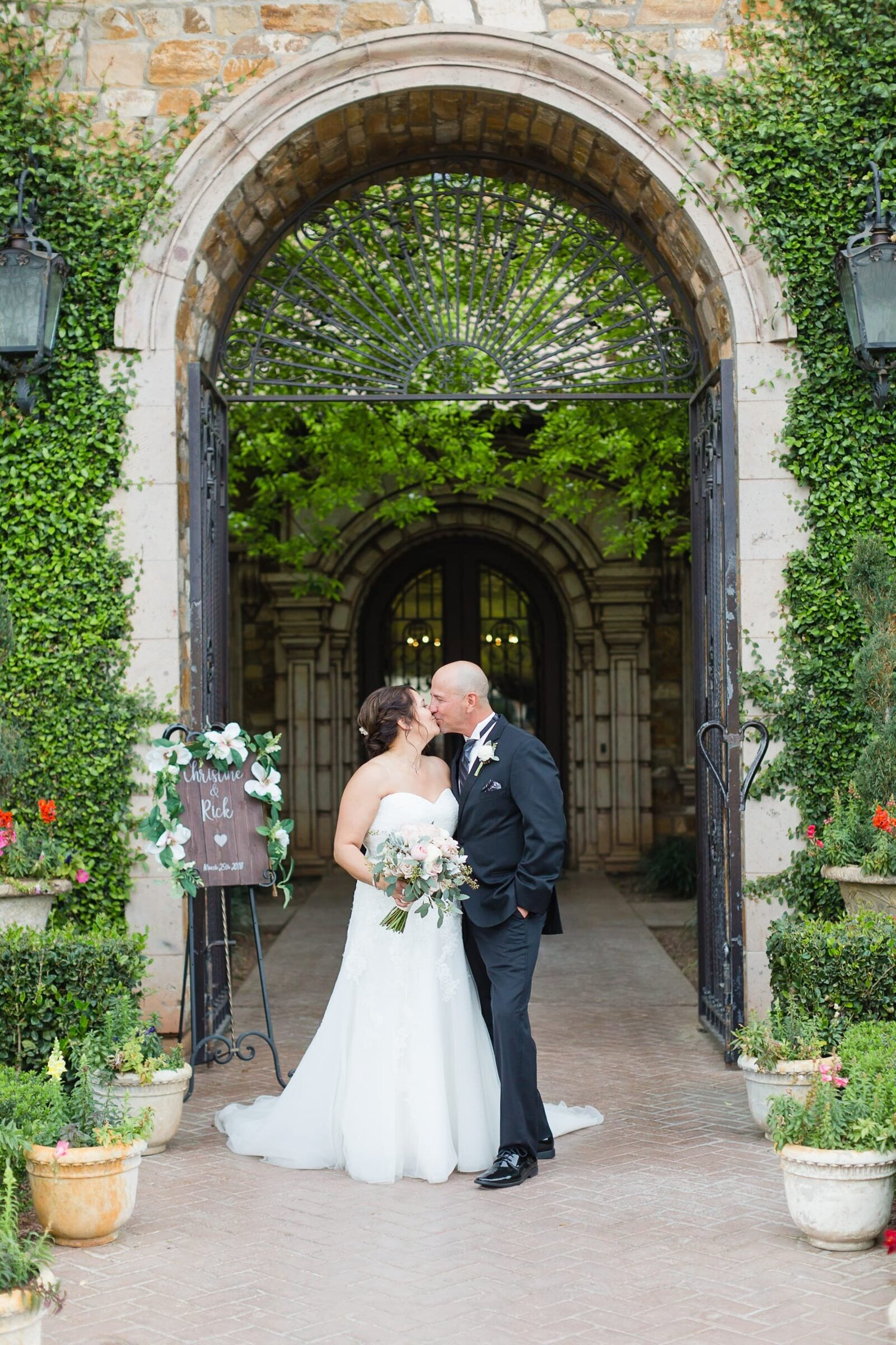 groom-and-bride-kissing-under-arch
