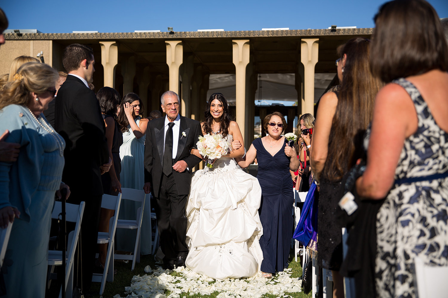 A beautiful Persian bride makes her way down the aisle with her parents