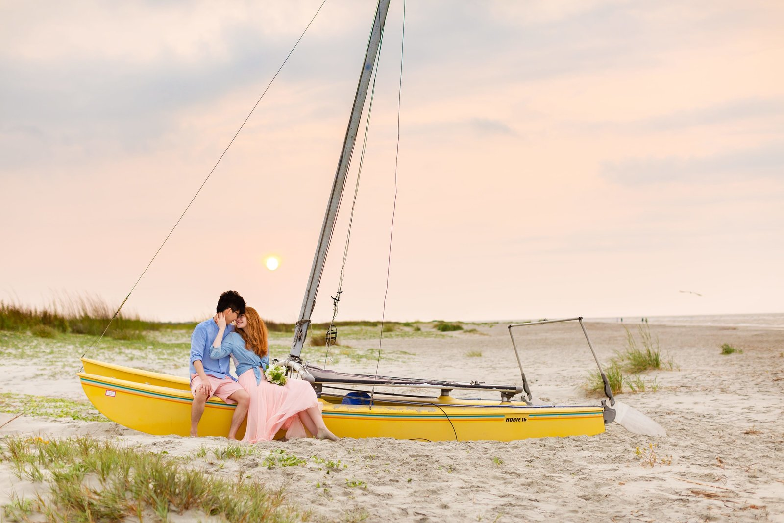 couple poses at the charleston  beach on a bright yellow sailboat while sharing a laugh together