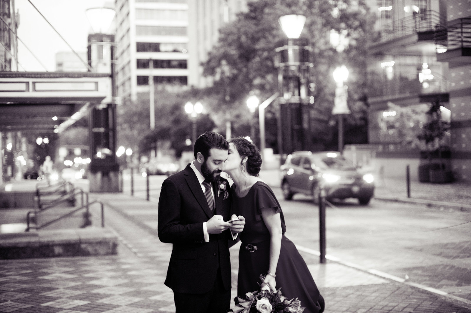 bride kisses groom on street at night in downtown portland