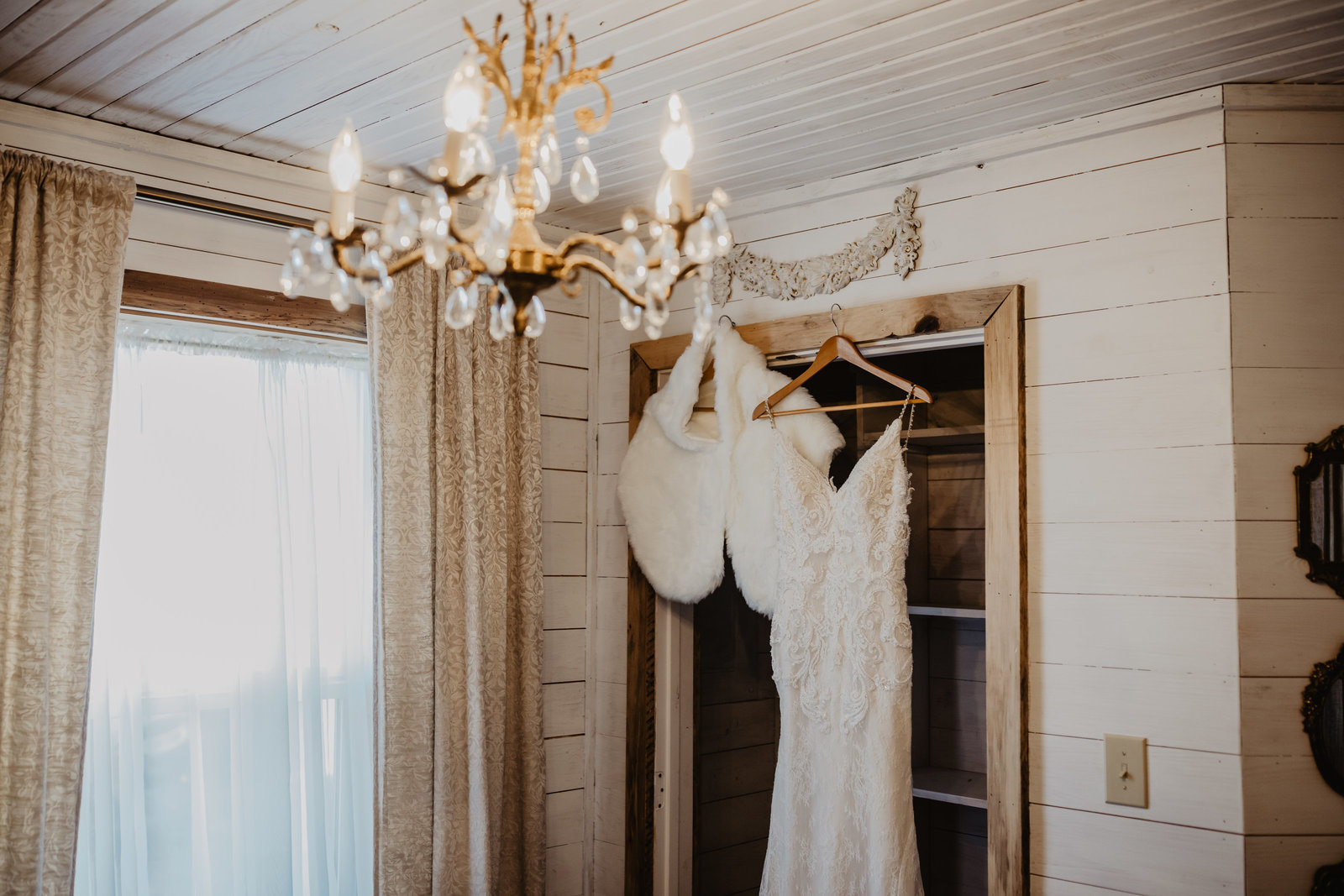 Wedding dress hanging in rustic bridal suite at Apple Ridge Farms.