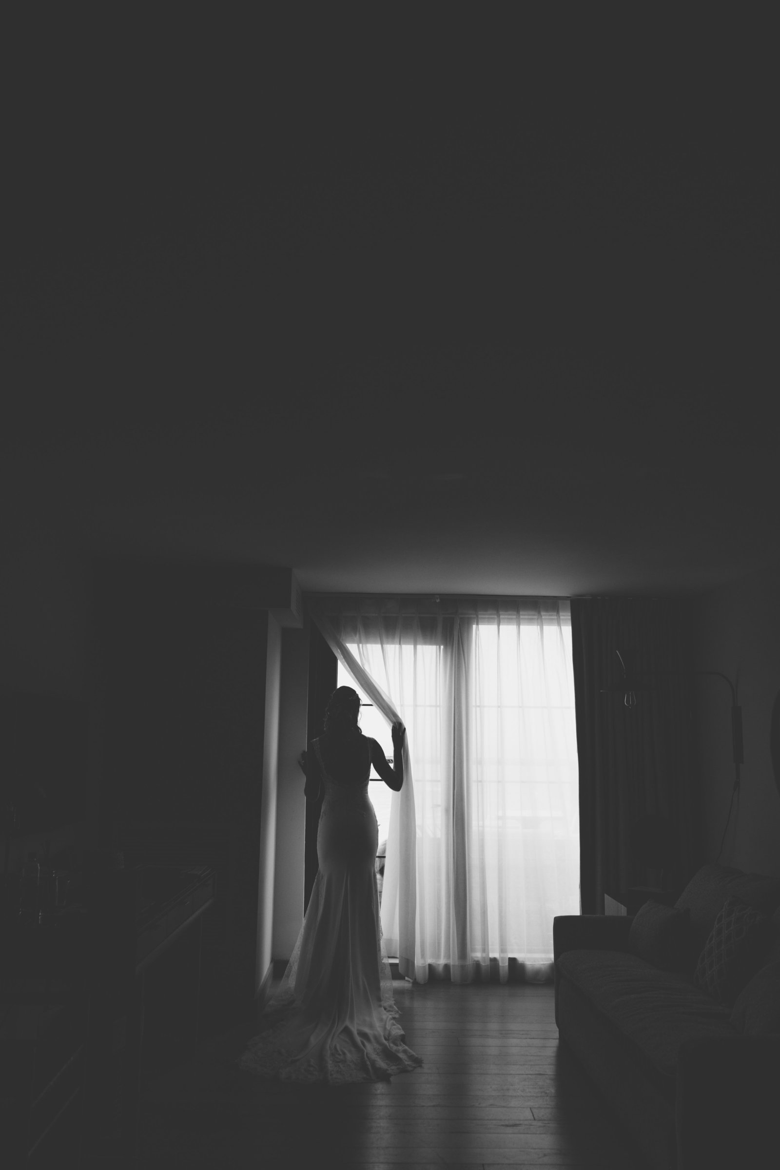 black and white photo of bride looking out the window at  Gurneys Montauk Resort wedding