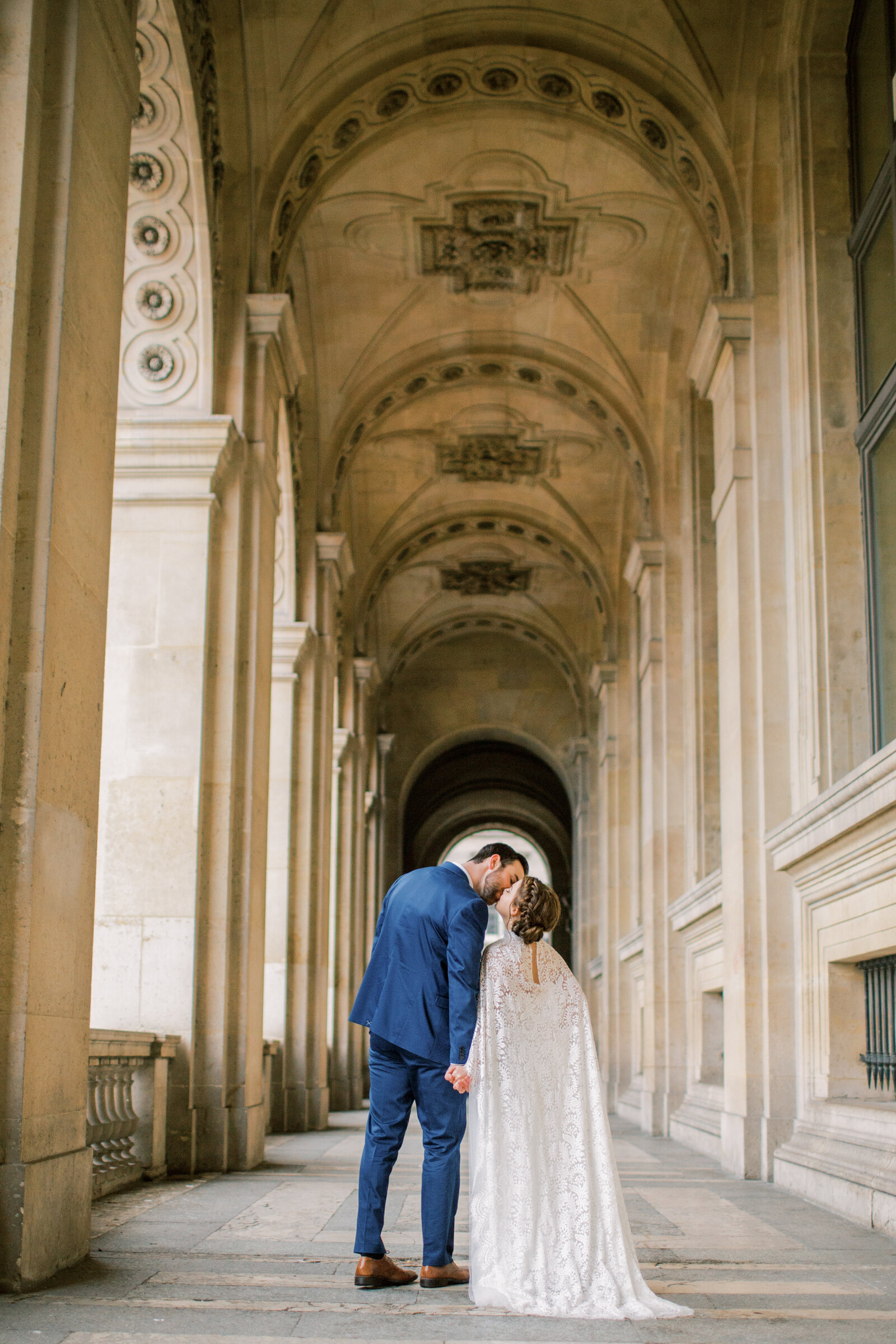 bride and groom kissing under arches in paris france