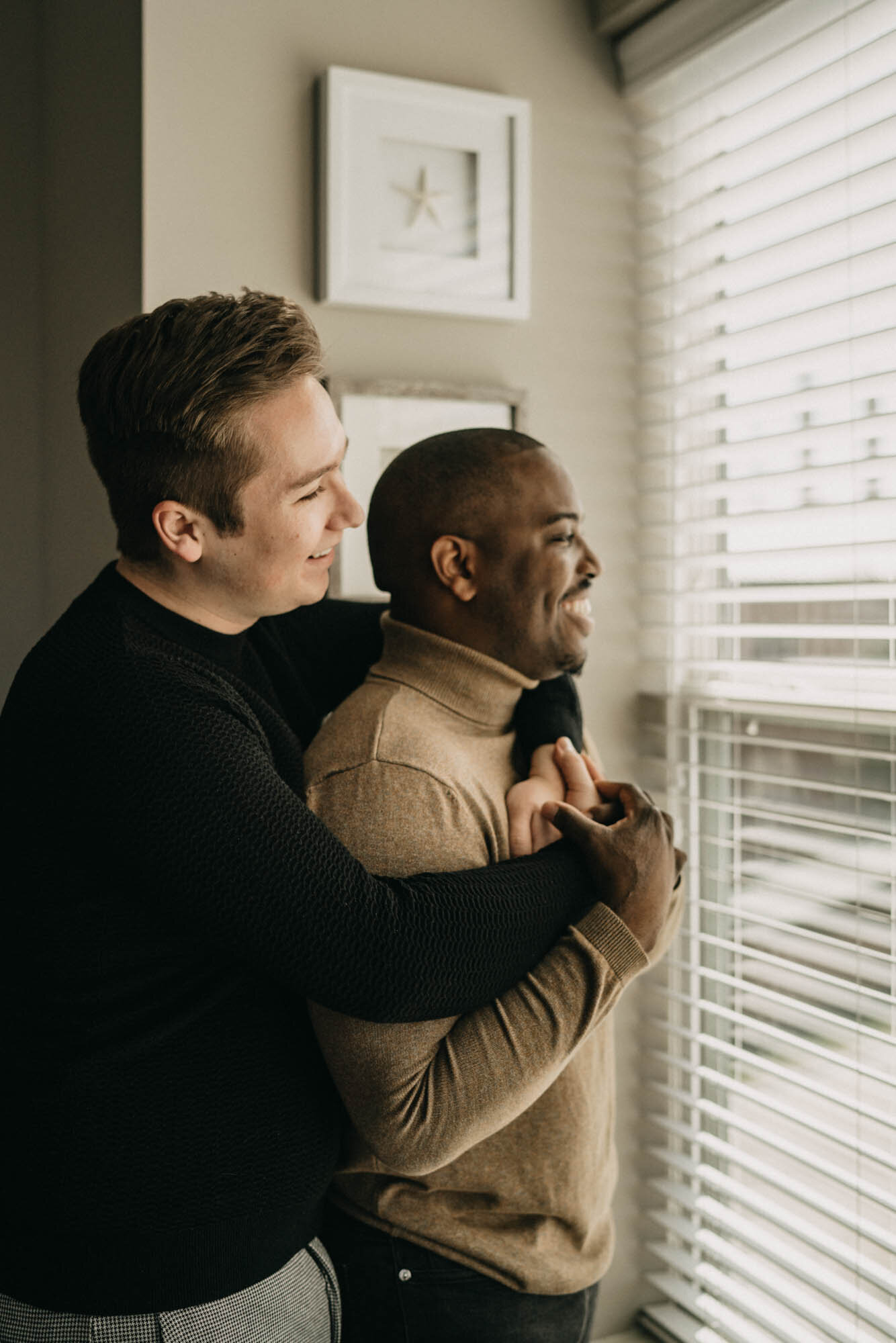 lgbtq couple cuddles by window during in home session in kansas city